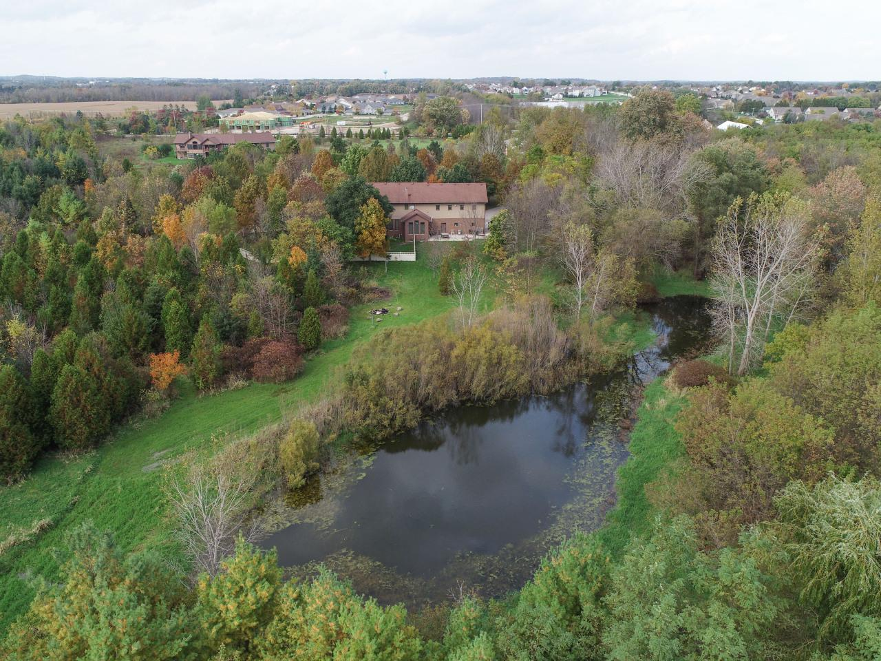 This is your chance to own 24 acres of paradise! Enjoy the abundant wildlife, hiking and hunting. Sip your morning beverage while watching the deer, turkey or the birds in the pond. Take a hike and stop at the creek. Custom built brick home features solid oak flooring, custom mill work, built-ins, Pella windows and much more! Huge bonus room above garage with new flooring. Freight elevator makes moving large items to the second floor a breeze. 30x50 and 25x30 pole buildings for plenty of extra storage. Recent updates include granite counter tops in kitchen, air conditioner, furnace, refinished hardwood floors on main, whole home generator, air exchanger, Weather Tight front door. Kubota tractor with brush cutter included. HSA Home Warranty provided.