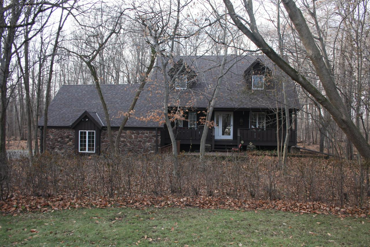 Charming, ''Storybook'' Cape Cod nestled in the woods.  Custom design for the person who appreciates quiet and natural beauty. Home surrounded by inviting front porch & decks.. Open concept! LR & FR  have authentic wood beams & gleaming cherry floors w/ a stone gas fireplace.  Dining Rm has original pegged oak floors and opens into gleaming sunroom w/windows on 3 sides. Views of woods are breathtaking!  Upper level has three spacious bedrooms, two full baths, master suite with WIC and dressing area.  Sunny kitchen w/newer stainless appliances, breakfast bar and open to dining area.  Office/ den on first floor.  Huntington Park is just a walk or bike ride away from Lemke Park & Mequon Nature Center.  Walk-out basement & RR.  Excellent Mequon-Thiensville schools. Roof 11/2018, tear-off.