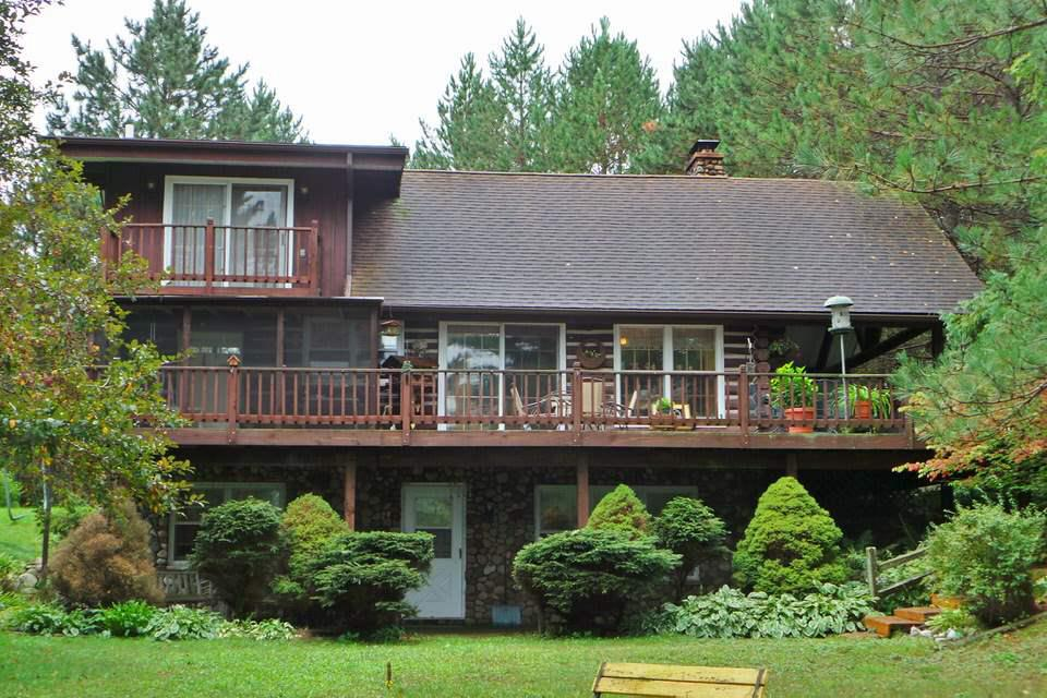 This beautiful full log home features beamed ceilings, knotty pine walls, parquet and wood floors. It has a full, finished lower level with a walk-out to a patio facing the lake. There is a huge covered wrap around deck. It has 3 bedrooms, 2 baths and 2 fireplaces. There is a detached 2+ car garage and a garden shed. The setting is glorious. It is wooded, rustic, private and beautiful. There is over 530' of frontage on Lake Romeo.