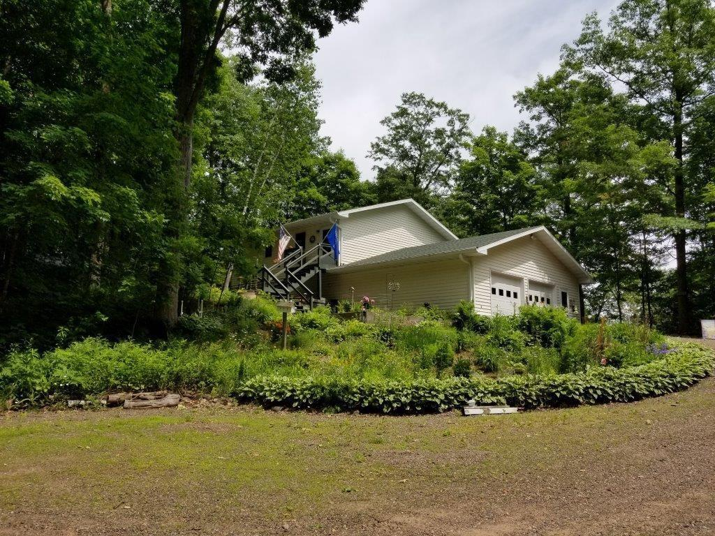 Looking to be tucked away in the woods, yet have easy highway access to Spooner or Rice Lake, if so this amazing listing is just the spot.  Home offers 2 bedrooms, 2 baths overlooking your 385' of shore line on Lutz Lake which offers plenty of pan fish for your enjoyment.  Kitchen opens to cozy living room which connects to your screen deck or master bedroom.  Come relax & enjoy the call of the loons from your deck or family room.  There is plenty of storage room in the lower level, and the garage provides extra space as well.