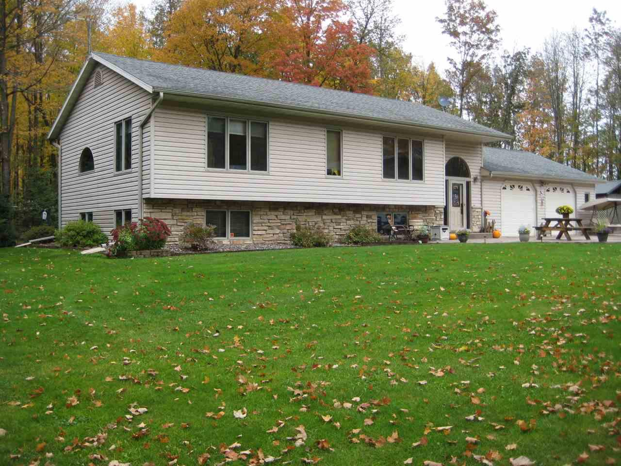 Immaculate 4+ bed, 2 bath country home on +/- 14.92 wooded acres. Beautiful kitchen with new appliances, breakfast bar and pantry. Large master suite with private master bath and walk-in closet. Newer addition features a family room with vaulted hickory ceilings and covered deck with scenic views. Finished lower level. Attached insulated and heated 2+ car garage, 32x24 shed with lean-to. 20x12 and 15x11 additional storage sheds. Conveniently located 4 miles from town on a blacktop road. The land features a trail system and is nicely wooded. The stove, refrigerator, microwave, dishwasher, washer, dryer, window treatments and LP tank are included in the sale price.