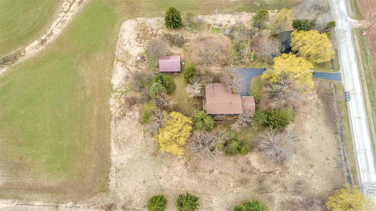 Hobby Farm on 4.25 Acres & 30X20 barn included.   Quiet setting with small orchard, grape vines, pond & perennials.  Custom Built in 1976 with wrap around deck & 3 sets of patio doors. 4 bedrooms & 3 full baths & 2 1/2 baths, formal dining, eat in kitchen w/center island & granite counter tops,  lrg sunken great room 21x20 w/floor to ceiling field stone fireplace, front sitting room/den and family room w/soap stone wood burning stove. Main floor has extra office w/ separate entry could be in-law  suite or other.  1st flr laundry room between suite & house, & unfinished walk out lower level!
