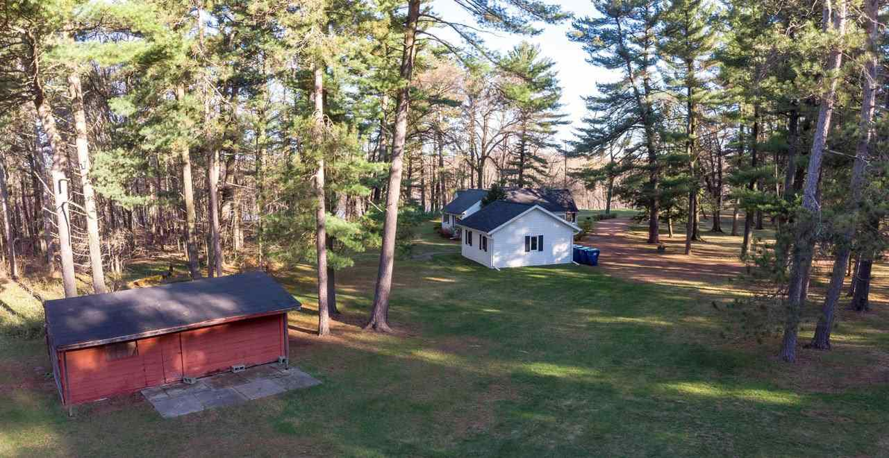 Build your dream home on this beautiful 11.17 acre waterfront property located on the Wisconsin River with over 1400 feet of waterfront. This lot is partially wooded with a nice grassy area and a storage building where horses once grazed. Nestled along the circular driveway is a quaint cottage home that could be used as a guest house with a detached garage built in 2011.,Property is being sold AS-IS due to low price with this amount of acreage and water frontage. The adorable home welcomes you in with a beautifully laid brick patio to a cute 3-season porch. The home features a kitchen and dining area with large windows, a full bath with tile flooring and tile surround in tub/shower. There are 3 bedrooms with one featuring the ultimate built-in library of bookcases, cabinets and windows. The den features a stone-faced fireplace with a wooden mantle and has an additional 3-seasons porch that looks out into the backyard. Step down from the den into the sunken living room that gazes out over the Wisconsin River and the beautiful acreage this property has to offer. With so much potential and such a desirable location, this property is a MUST HAVE in the D.C. Everest school district.