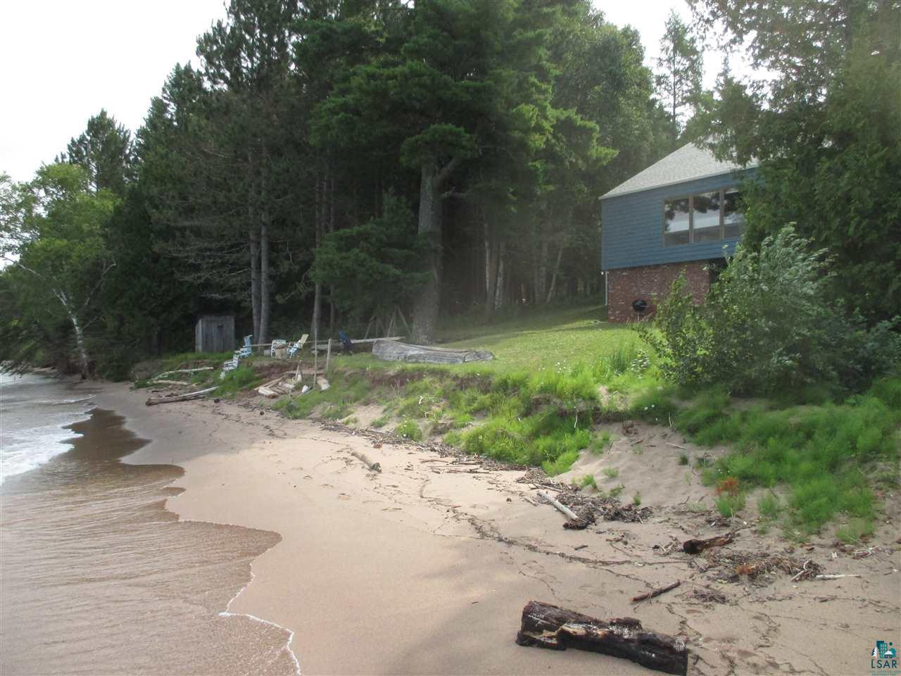 This is truly a rare opportunity to own over 2,000 feet of sand beach on Lake Superior, just 1/4-mile from the Apostle Islands National Park - Meyers Beach headquarters. You can see the famous Sea/Ice Caves, plus Eagle & Sand Islands & the North Shore. Listen to waves lapping along the shore just steps from the solidly-built home. This is a nature-lover's paradise! Hike the beach, enjoy kayaking, paddle-boarding, fishing, & sail from the Marina at nearby Cornucopia.  Immerse yourself in the quiet beauty of ~38 acres of private mixed forest, including a beautiful White Pine & Red Pine forest with fragrant needles & a soft forest floor. Enjoy birding among the cedars, aspen, maple, birch & spruce, star-gazing, Northern Lights, gorgeous sunsets & more. The home has a cabin-like feel with some pine paneling & kitchen cabinets, and a Great Room with a wall of windows to the Lake. The 3-Season Porch will become your favorite room! Plenty of bedrooms plus a full walk-out basement. Keep your small watercraft & beach toys in the Boathouse. You can use the outbuilding for storage or easily convert it to a garage. With this privacy, shoreline & ideal location near Cornucopia & Bayfield, you can be refreshed & find your peace all four seasons!