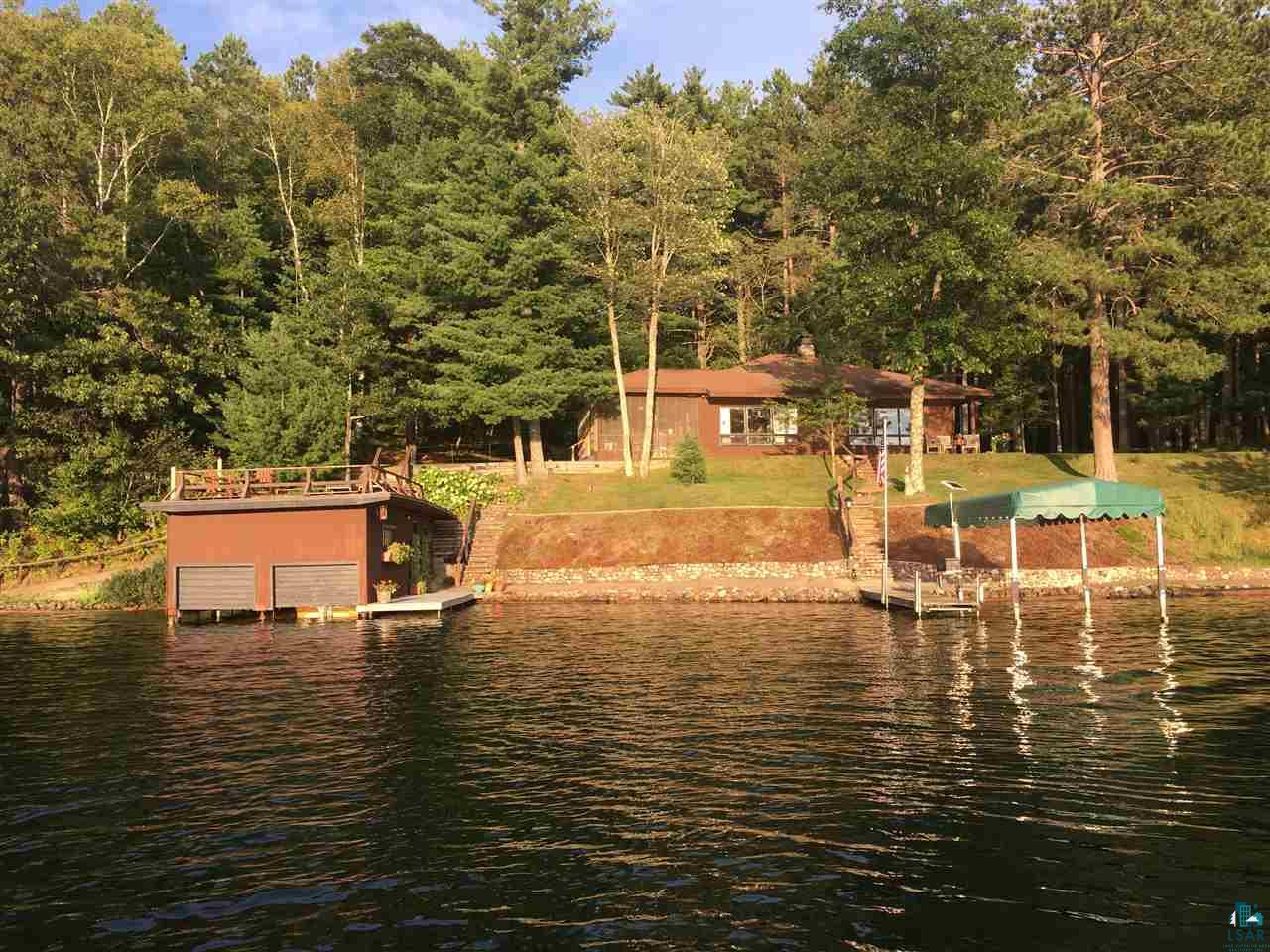 The perfect lake setting, close to the water with Western/South Western exposure for maximum sunshine and incredible sunsets.  4 BD, 2 bath home with partial basement that also has sleeping space.  Enjoy one of the nicest swimming areas on the Pike Chain of Lakes.  Boathouse fits 2 boats and has a wonderful sauna, and sundeck above.  2 car garage and large lot with towering pine trees affords maximum privacy!