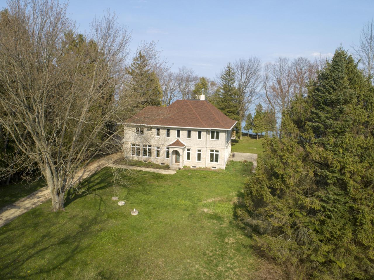 7.89 acres of Lake Michigan frontage offers the perfect setting for this outstanding 4 bedrooms, 5 1/2 bath residence. Enjoy lake views from every room in the house. Hardwood floors throughout the open concept LR and DR. Private office, spa room with hot tub, sauna, and full shower, chef designed kitchen. Four large bedroom suites with lake views, walk-in closets, and private baths. Finished lower level. A large outbuilding with tall doors is perfect for a car collection or a boat and is located as you enter the property along with a separate residence that can be remodeled into guest quarters. 25 minutes from downtown Milwaukee.