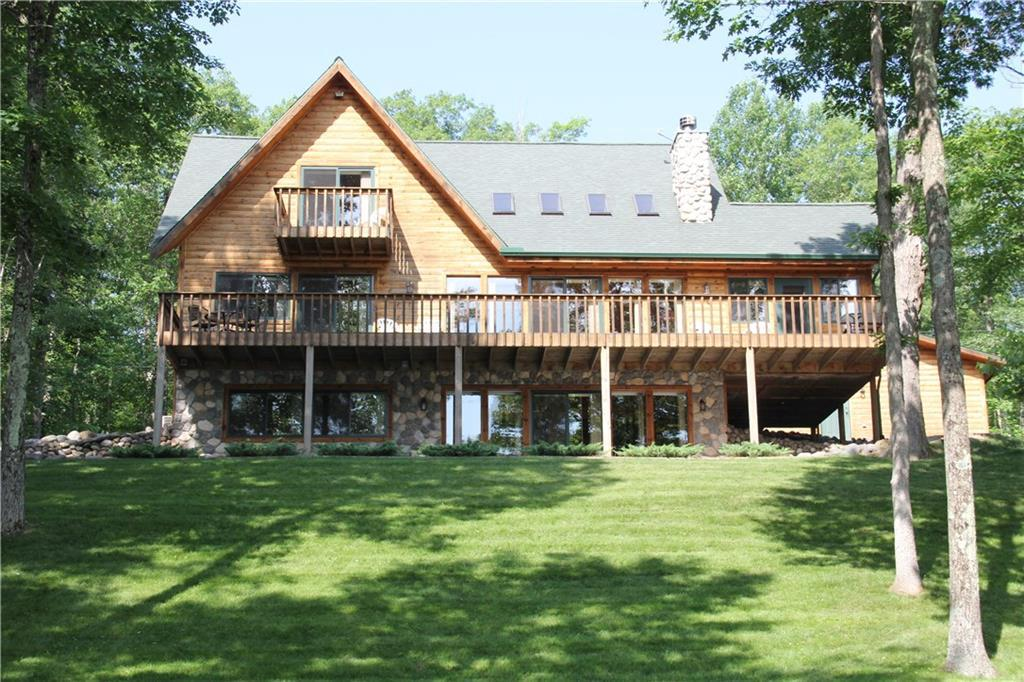 Beautiful log sided chalet w/3 bedrooms, 3.5 baths, great room with vaulted ceilings, 2 fireplaces, spacious lakeside deck & detached 4 car garage.  Situated on private wooded lot with 100' frontage & 3 acres.