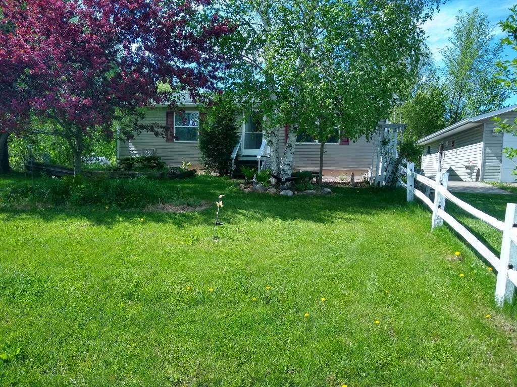Tucked into a private setting along Hwy 8 is this cute 2 bd, 1 1/2 Ba 2002 manufactured home w/ a full partially finished bsmt. This home sits a fair distance off the hwy on 13 wooded acres to be enjoyed for hunting, recreation or for raising a few horses or beef. There is ample storage in the 30' x 40' detached garage which is connected to the house by a large cement patio providing a great relaxation area. All living facilities are located on one level for life simplicity.