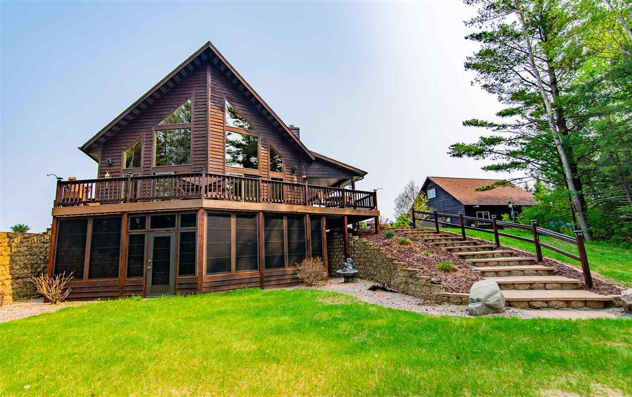 """This stunning house set on 5+ acres on the Spirit River Flowage can be yours today!  A custom-build home with attached 2 car, and Detatched 2-car garage/workshop is a Northwoods gem!  This property is in pristine condition and has been well cared-for since built.  This property features 200 feet of water frontage, 2x6 sidewall construction, a 28x36 heated detached garage with a loft, a gorgeous 3 season porch off of the walk-out basement and includes a hot tub.  You must see it in person- it's perfect!,Horseshoe pits, multiple fire pits- one of which includes a stone patio with furniture!  The lot features Apple trees, Grapevines, worm beds, scenic views and a gentle slope down to the water.  All of this mixed with the integrated inside and outside audio system make this a Northwoods paradise!  Sale also includes all barstools, a patio heater, pool table and exercise equipment.  The roof on """"everything"""" in 2017.  The house and deck were professionally stained in 2017 also.  Tv's in the house as well as the pontoon on the property are available and negotiable in price."""