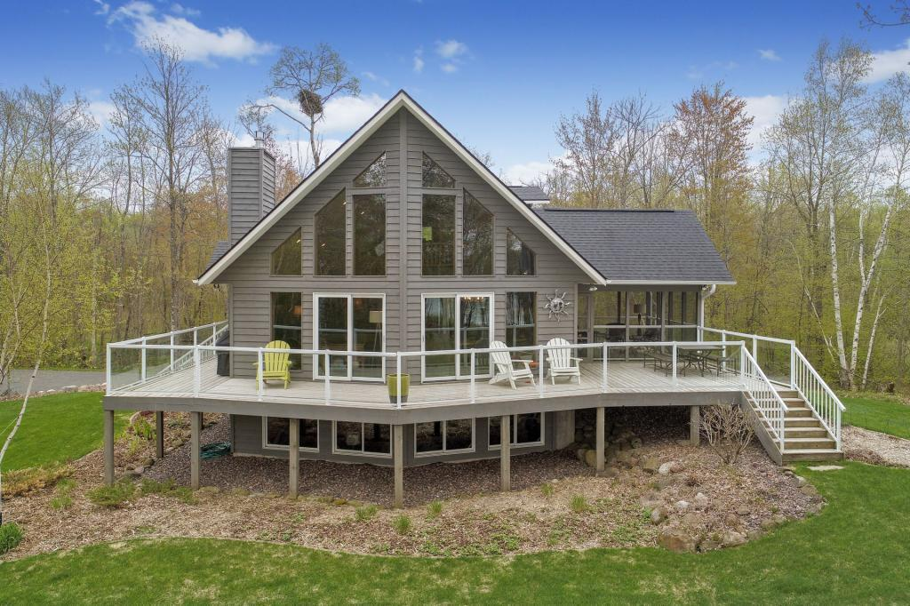 Stunning cedar chalet on the shores of Chetac Lake. Over 435 feet of frontage and 3.56 wooded acres, westerly exposure and perfect elevation. Turn-key home includes high end furniture and furnishings along with dock. Features include: gas log fireplace, hickory and tile flooring, elder cabinetry, granite counter-tops, glass deck railing, central vacuum, loft level master suite, three season room, wrap around deck and unfinished lower level walkout. Enjoy the serenity, nature, water sports and access to all-season recreational trails this spectacular home has to offer.