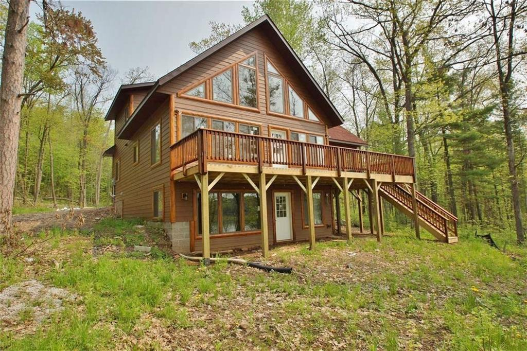 Slim Lake--Enjoy a brand new chalet, low maintenance siding, southern exposure & easy elevation to the sandy shore of the full recreational lake. 3 BR/2 Ba cabin has an open concept LR, kitchen dining area and 2 BRs/1 bath on main floor, master suite on 2nd floor & unfinished basement. Large screen porch and lakeside deck. The 0.93 acre lot has 137 feet of shoreline. Easy access to Stone Lake. Cabin finishes almost complete--will be move in ready. Adjacent lot for sale. Land contract available.