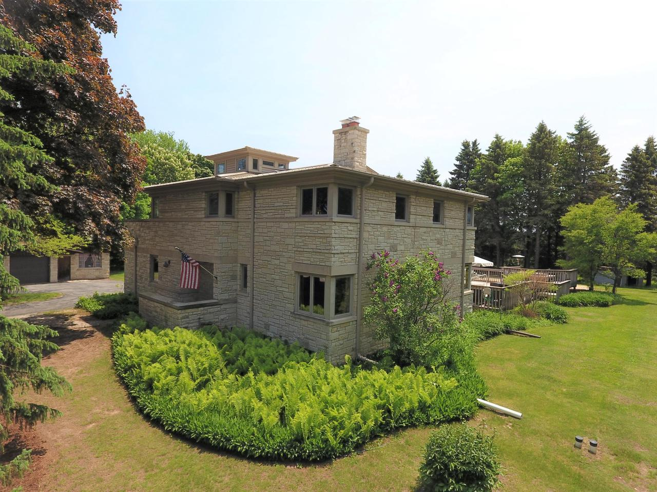 First time offered this Town of Grafton Frank LLoyd Wright Style home is among only a handful in Wisconsin. Private 2.18 Acre Yard abuts park. Impeccably maintained: inground salt-water pool 2012; spa 2017; PVC deck 2012; steam boiler, piping, expansion tank 2013; tear-off roofs 2011; 200 amp upgrade; mound upgraded. Rooms feature old-world craftsman plaster walls, a custom Venetian plaster finish in main bath & includes a heated towel rack and all Kohler Memoirs fixtures, original crown molding, baseboards. Birdseye maple hardwood floors are found throughout the residence.Original lannon stone fireplace. 2nd floor has 4 brms, 3 with porcelain sinks. The 4th brm up reveals an unaltered mural painted by a local artist. Additional staircase to 3rd level watch tower.