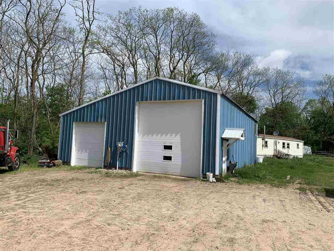 Nestled in the hills of Juneau County, approx. 26 acres with a multitude of uses! Bring the ATV's, horses and cattle or just relax in the country.  36'x40' heated shop with a parts room, upper loft, office and bathroom. Another shed used for hay/wood storage and a mobile home. Newer well & septic. Enjoy it just as it is or remove the mobile home and build your dream home!