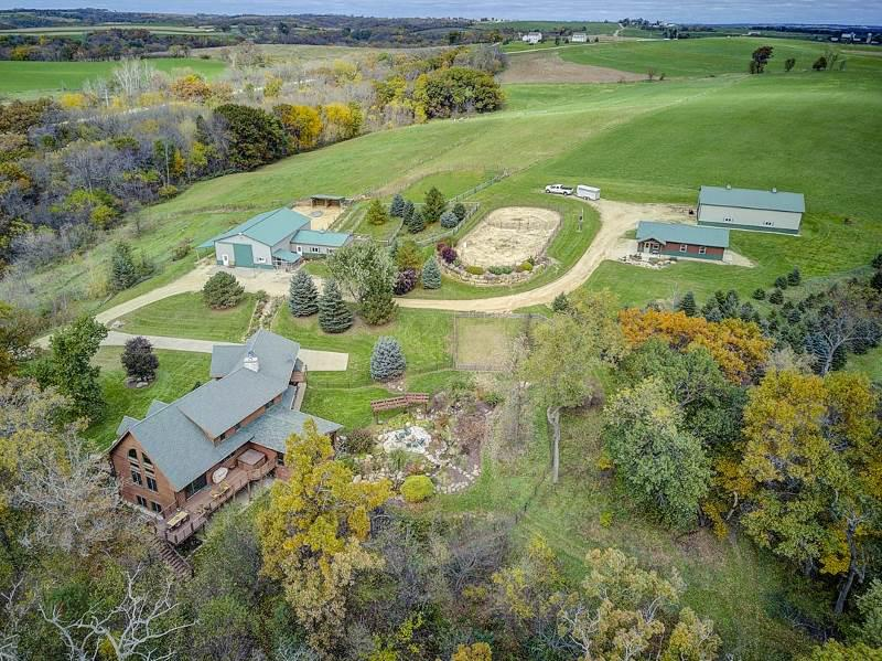 """MRP $895,000 to $1,095,000. Secluded,park-like setting of 80 acres horse/cattle ready. Consists of 15 in hay, pastures, paddocks & outdoor arena,30 in woods w/ trails, pond,organic garden. Thoughtfully planned & custom designed home has the beauty of cedar log ext.(Thermal-log design)w/ traditional 6"""" studded const. Offers soaring beamed ceilings, solid Walnut, Hickory & slate flooring, 6 panel oak doors, craftsman style lighting, elegant chef's kitchen w/ granite & Viking professional stove/ovens. Perfect oak shaded porch for sunsets & babbling stream wrapped stone patio for moon rises. Only 9.5 miles S of Hwy 18-151, apx 30 mins to Madison."""