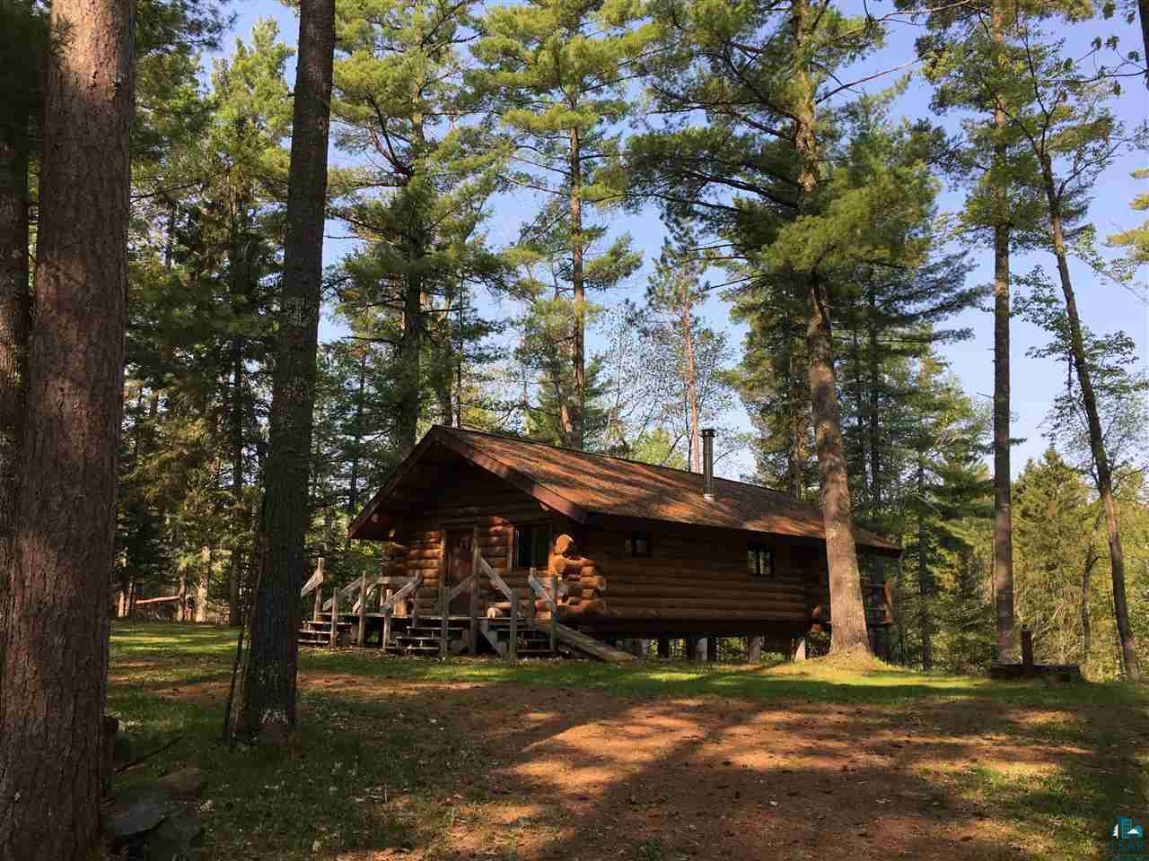 "If you are looking for a forever log cabin, look no more! This beautiful and serene property under 80' virgin pine, home to all of Wisconsin's wildlife and filled with bird song, gets you ""away-from-it-all"". It has one big open floor, this settler?s style cabin with high ceilings, and hardwood floors. It is warmed by a wood stove with catalytic converter, which heats the place like a charm! The kitchen corner is roughed in and not yet hooked up. This gorgeous structure has 4 bunk beds, so you won?t miss a thing until the last person goes to sleep.  During the warmer months, live, read, write and simply enjoy the huge covered deck watching the bald eagles sore and fish for steelhead or rainbow trout in the Cranberry River below. Or walk down and fish yourself! This property comes with detached garage / wood shed, where the composting toilet has it's private 6 x 10' space as well. There is an amazing flowing artesian well that pumps 50 degree clear and fresh water non-stop, 30 gallons a minute. Seller says it's like heaven's champagne! This well, close to the house could be the ready-to-go source of water for the home to be plumbed in.  The house would easily allow for an added walk-out basement.  All the structures are wired, but currently pulled off the grid. These 39 acres are located on a country road in the South Shore School district and zoned Forestry-1. There is roughly 550' of frontage on the Cranberry River, which is a class A trout stream. Seller says you have to experience the peaceful feeling this property brings to the soul, he says it's hard to describe in words.  There is little to no cell-service in this area, but fiber-optic internet at the road. Call for additional information and to schedule an appointment."