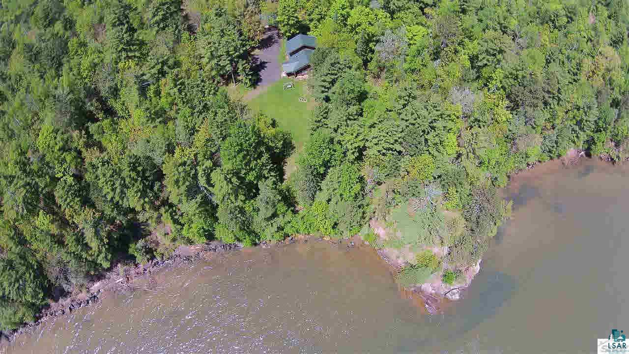This truly one of a kind Lake Superior log home has it all! Very rare find with your own private brownstone point for swimming, kayaking, or just relaxing! This log home is surrounded by forest so no visible neighbors. Everything throughout the home has been update with quality. Custom logs, cathedral ceilings, panoramic views of the lake, main floor bedroom, cherry kitchen cabinets, beautiful fireplace, enclosed library area with sauna that overlooks the seasonal creek, open stairway that leads to the upstairs with 2 bedrooms, 1 bath, and another bonus sleeping area in the loft. New on demand boiler that services the infloor heat. Detached 2 car garage and one other storage building.  375 ft of Lake Superior frontage