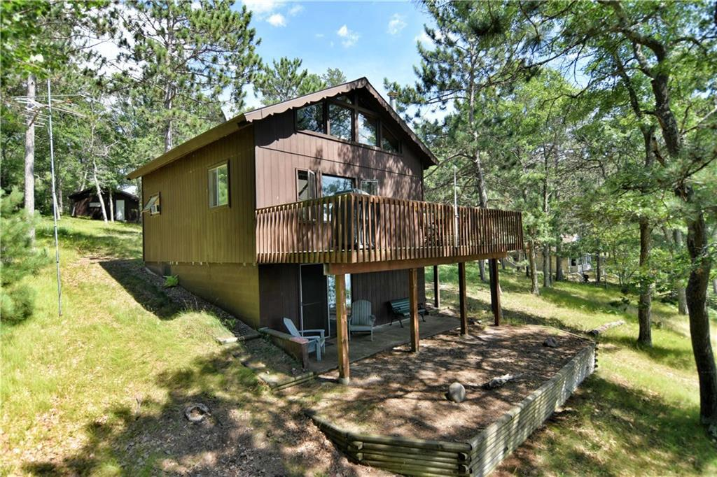 What a setting..121' of sandy beach overlooking one of the islands. With western exposure, the wooded lot sits on one of the widest parts of the Flowage.  Sit on the deck to watch the sunsets which can become your favorite habit.  2+ bedrooms and 2 baths.  Living room with wood stove has windows to the lake.  3 season porch.  Large loft is divided into 2 sleeping areas. Walk out basement.  Single garage plus  30 x 56' pole building with workshop and heat.  A perfect lot for perfect cabin living.