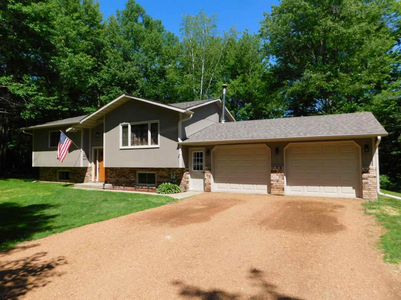 Awesome kitchen with brand new quartz counter top, tons of cabinetry, open to dining and patio doors to back yard deck. This spotless country home on 36 acres, is located just minutes north of Merrill. The Main floor offers kitchen, dining, and living, along with pretty tiled bath, with jetted tub, and master bedroom with huge walk in closet. Lower level has 2 more bedrooms, second bath, family room, and walk out to the back yard. The laundry has nice cabinetry and very comfortable. 2 car garage.,Outside you will find a small storage and 36.71 acres. Wooded around the home, with room to hunt right at home, with about 7 acres of field for some gardening, or rent out to the local farmer.