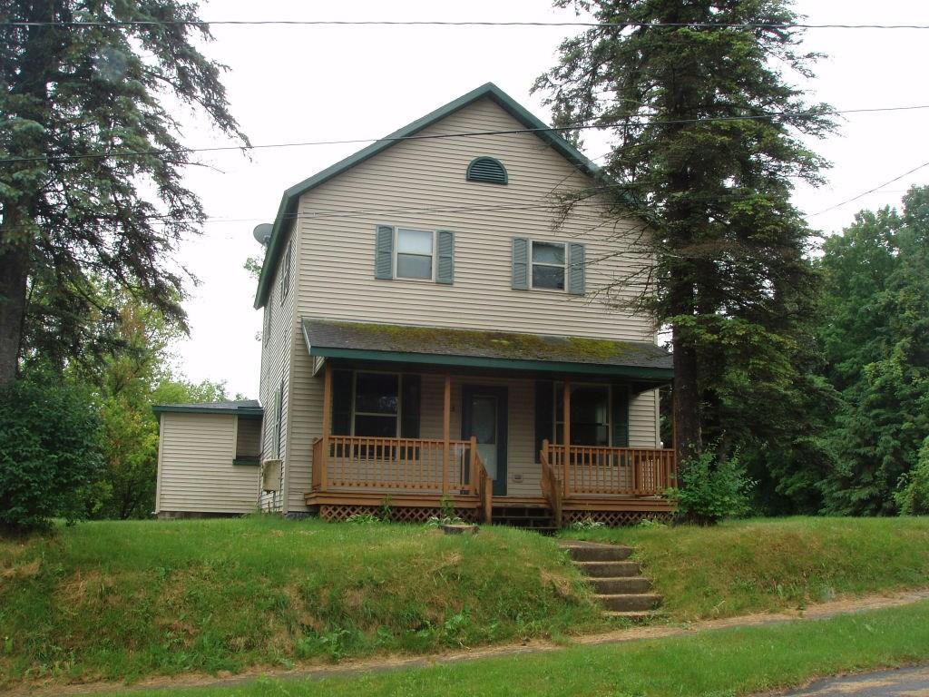 (354) Family sized 4 BR, 2 story home is located on the corner of Hwy. 13 and W. Illinois Street in Butternut. The main level features roomy kitchen with oak cabinets, 1st floor laundry room with closet, formal dining room featuring wood floors and high ceilings, and a living room also featuring wood floors and access to front covered deck. There is a handy  bath on the main level. The rear porch which is enclosed has an additional storage area. Upper level features 4 bedrooms and a full bath. Some painting has been done and the wood flooring is painted. Full stone basement has interior and exterior entrances, has a Weil McLain boiler furnace, electric hot water heater and circuit breakers. The exterior of the home has vinyl siding, vinyl windows and composition shingles. The property is serviced by municipal water and sewer. There is a small metal shed. All this located on a 200-foot deep parcel with 76 feet of frontage on W. Illinois Street. Priced to sell at $43,900. (21-41N-1W)