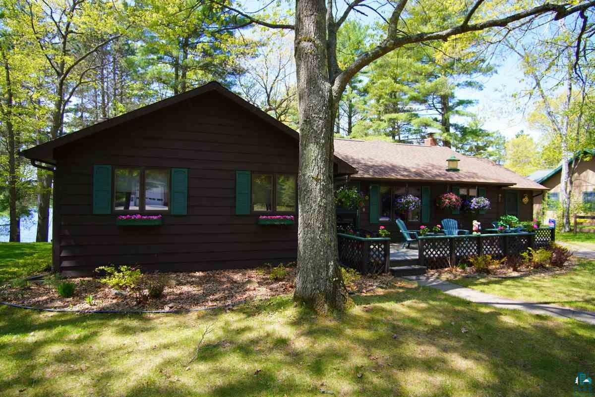 """This is a very special lake front home on Lake Nebagamon.  It has great windows that face west, beautiful views.  There's a great master suite, a 12' x 22' sunroom overlooking the lake.  There's several decks, a screened-in Gazebo, and a 90' dock. The home was completely remodeled. Recent updates include a new roof on the house & gazebo, both bathrooms updated, and slate tile floors, new hardwood oak doors throughout home in 2015, beach storage building built in 2012, sunroom and decks in 2004.  The two-car detached garage with power, a storage shed, and a drive-through """"C"""" paved driveway in the front of the home. There's gorgeous mature trees, landscaped yard with perennials flowers, a beach storage building with power and lake pump, which is located at the water's edge by the fire pit and the 90' roll-out dock , with water depth of 10' at the end of the dock.  This is an energy efficient home with low utilities, a newer furnace, central air, water heater, 200 amp service, conventional septic system and well.  The school system is the Maple School District.  Lake Nebagamon is a 986-acre lake with a maximum depth of 56' and it has a sandy bottom.  It's a popular fishing lake providing panfish, large & small mouth Bass, Northern Pike, Trout and Walleye.  The Village of Lake Nebagamon is an active community, celebrating several events throughout the summer.  They have a website touting the activities, at villagelakenebagamon.com"""