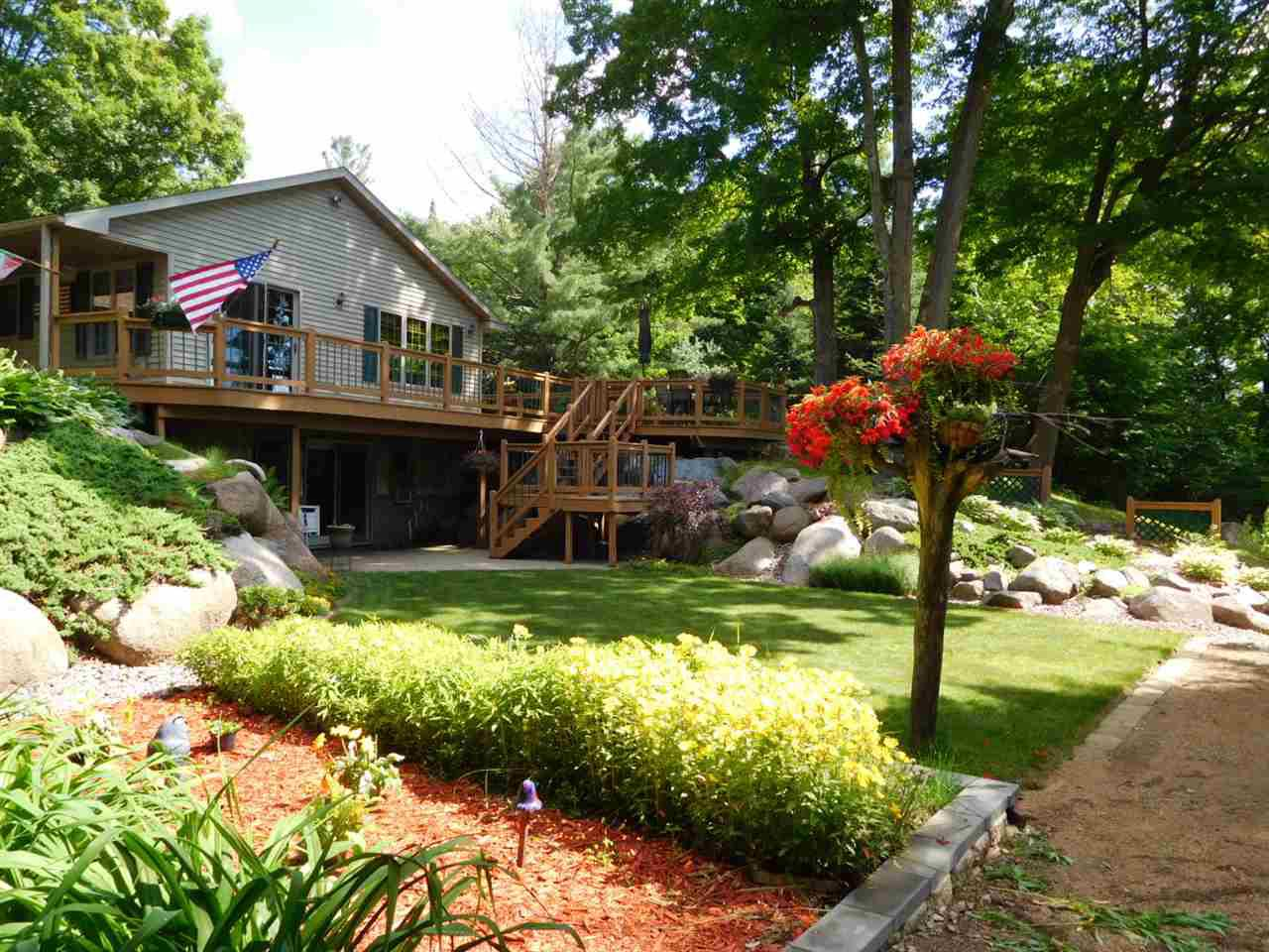 Are you looking for a very private setting with a beautiful wooded lot and meticulously well maintained home and landscaped yard? Well you just found it. The attached garage is finished and insulated with its own heating unit that is connected to the outdoor wood burner. Matter of fact the wood burner heats the home as well if you want to save on fuel costs. Two bedrooms, master bath, a half bath, laundry area all on the main floor. The lower level walk-out has another bedroom and full bath. The open concept kitchen, dining and living room all flow nicely together. There is another detached garage for storage and to house your outdoor equipment. A lean-to between the garage and home is the perfect place for your summer time grilling or just to relax in the shade. This is another move-in ready one owner home