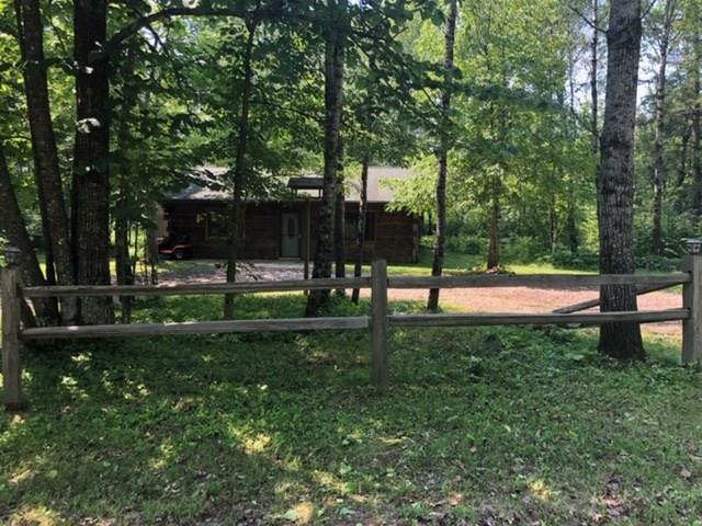 """Wonderful Opportunity to own a genuine Log Cabin. This Square Log home gives you the """"Woodsy Up-North"""" your looking for, but with all the conveniences.  In-floor heat, with new boiler to keep the temps inside comfortable, fueled by electric off-peak.  Views of the woods in every direction.  Large open floor plan to use how you choose.  The island is not stationary, so you can do as you wish.  The beautiful Oak Cabinetry nicely compliments the square logs and the custom window and door trims."""