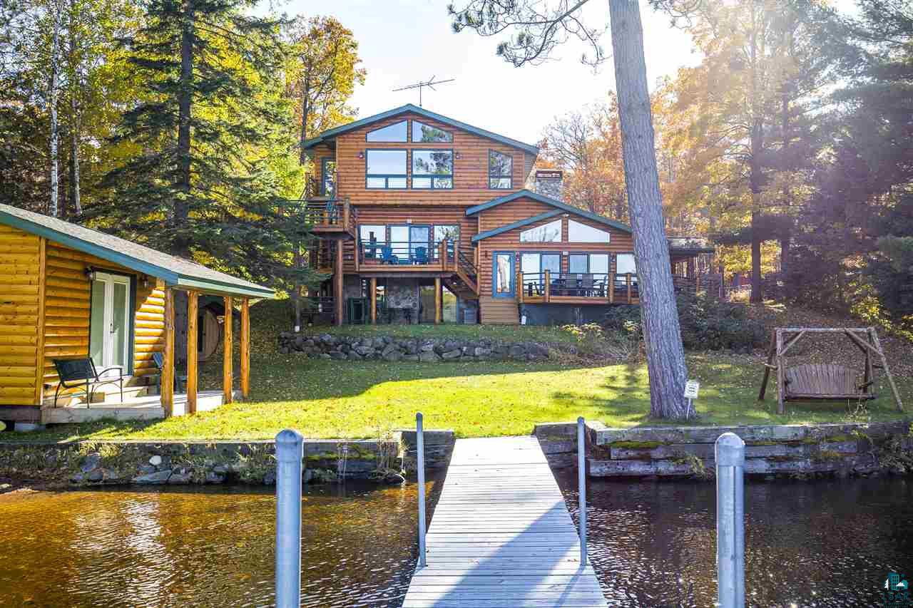 Do you love lake living? Extravagant 5 BR, 3 bath, log sided home on Lake Nebagamon. Walking into this home feels like your own private resort. The outdoor greeting space welcomes you with gorgeous handpicked logs & Lake Superior rock pillars. The main floor features a grand living room w/vaulted ceilings, wood burning fireplace, a 180 degree view of the lake, access to the deck, a full eat in kitchen, & a hot tub/party room. The 2nd floor features a bedroom w/deck access, additional sleeping space, & bath. The 3rd floor master suite is incredible w/vaulted ceilings, access to the deck, plenty of natural light, an electric fireplace, master bath w/double copper vanity sinks & a jetted tub w/ shower & tile surround. Also, on the third floor is another bedroom & a nice sitting area. The walk out lower level has a bedroom, bath, & laundry room. The attached garage feels more like an extension of the home w/heated floors, appliances & countertop space- a perfect space for large gatherings any time of year. Dream shoreline with 110 ft. of waterfront, a sandy beach & hard sand bottom shore. The steel roll out dock w/wood decking is also included. The matching log sided boathouse is 2 years old & fully insulated w/power.  Additional exterior features include an electric barrel sauna house & another 2-car detached garage that has 2 additional storage rooms. The sellers have used this property as a successful vacation rental when not enjoying it with family. So perhaps you want to use it as an investment. This home has been admired by many over the years, and now it can be yours!