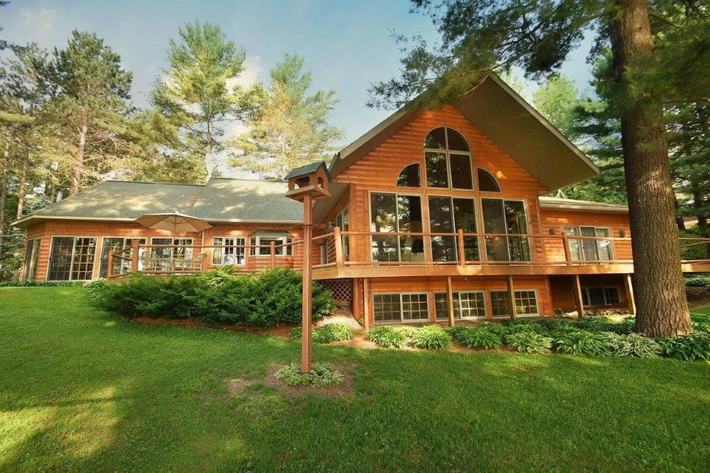 Stunning hand-hewn log sided chalet showcasing the history of Gatten Pt. Rd. peninsula on Warner Lake!  Classy 3+ BR, 3 BA, w/large sleeping loft, & master suite like you've never seen w/soaking tub, large walk-in closet, private office & gorgeous lakeside views. Large great room w/soaring pine ceilings, ledgestone natural gas fireplace, & wall of glass overlooking the lake and pines. Grand entryway w/8' door, cherry floors leads to an intimate kitchen w/lake views, granite counters, pine cabinets, pine beams, & 2 separate dining area. Fabulous grand 4 season porch w/9 gridded sliding glass doors brings the outdoors in. Lakeside views on both sides, floor to ceilings fieldstone LP gas fireplace! No expense spared from the 4-car att. gar., breezeway, massive log posts framing entrance, stamped concrete horseshoe drive, walkways, & perennial gardens pepper the lot w/pond & foot bridge. Lakeside deck leads to a gradual slope to 158' of sand shoreline, boat house & gorgeous easterly views.