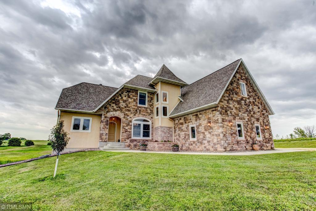 Beautiful custom built French Country style home.  Sits on 20 acres with 2 ponds and fruit trees.  Amenities include a chef's kitchen, formal dining room, main level master suite and a mother-in-laws suite on the upper level.  4 BR/3 BA.  Lower level has 2222 unfinished sq. ft - great potential for future rooms.  Geothermal heating/cooling systems.  Anderson A-series windows.  Covered porch leads to the large patio.  Great country location - 30 minutes to St. Paul.  Perfect for hobby farm, etc.
