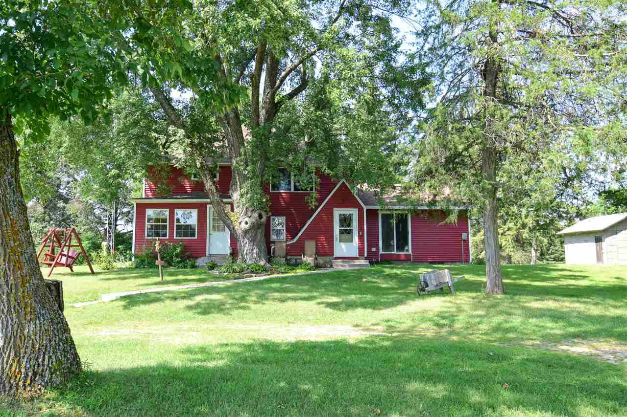 Country Charmer! New windows, siding, bath & sun room. This 4 bedrooms home features a bath on each level, Mst bath w/gorgeous tile work. Stainless appliances, breakfast bar & dinette. Huge dining room is great for entertaining, it's AWESOME right down to the new Edison light fixtures. 3 beds up, lg walk though w/plenty of room to wall off or use as family room/den. Several older outbuildings if you wanted horses, chickens, etc. pasture area could be fenced, det 1 car, Lg Spring fed pond w/creek going through corner of the property. Main floor laundry & wood furnace for extras too! Privacy galore w/no building allowed on neighboring 260 acres