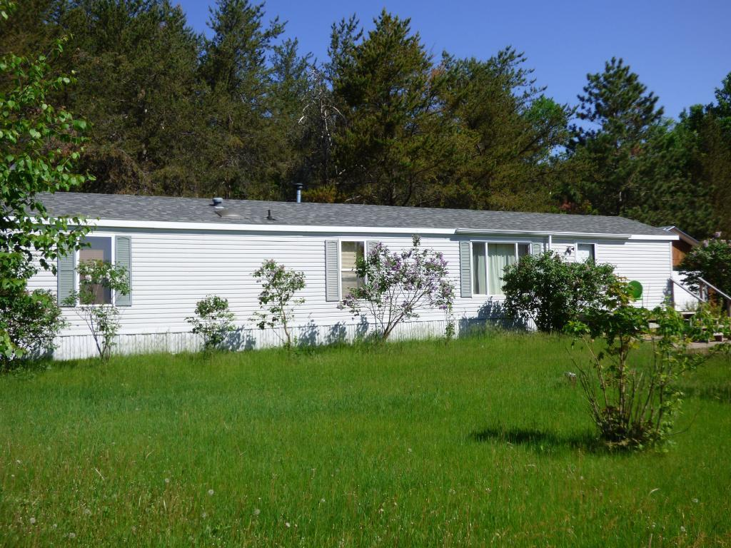 Blue Skies and open country here you come! Just 15 minutes from St Croix Falls and only a couple miles to Governor Knowells Horse Riding Trails. Well maintained and cared for, it was a brand new 1996 unit installed in 2004,  the roof is newer, only two years old- fabulous 2 1/2 car garage- there is plenty of room for a shop and your cars or if you are a big truck guy- there is room in this one. Has a nice shed and richie waterer. Drilled well. Open design kitchen-with eat in counter or dining area.  All living facilities on one level. The price is right for this one today!