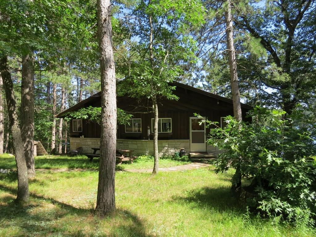 Diamond in the rough! Chalet style property on sought after Webb Lake w/ 150' of beautiful sandy frontage, gorgeous easterly views, & plenty of room for friends and family. Cabin features open dining & living space on the main w/ 2BR & family room below w/ 2 sleeping spaces & a walkout basement. Huge garage w/ loft space that could be finished into additional rec space, and additional storage below. Storage shed near the lake for all of your lake toys, & LG yard for outdoor entertaining. Near ATV & snowmobile trails!