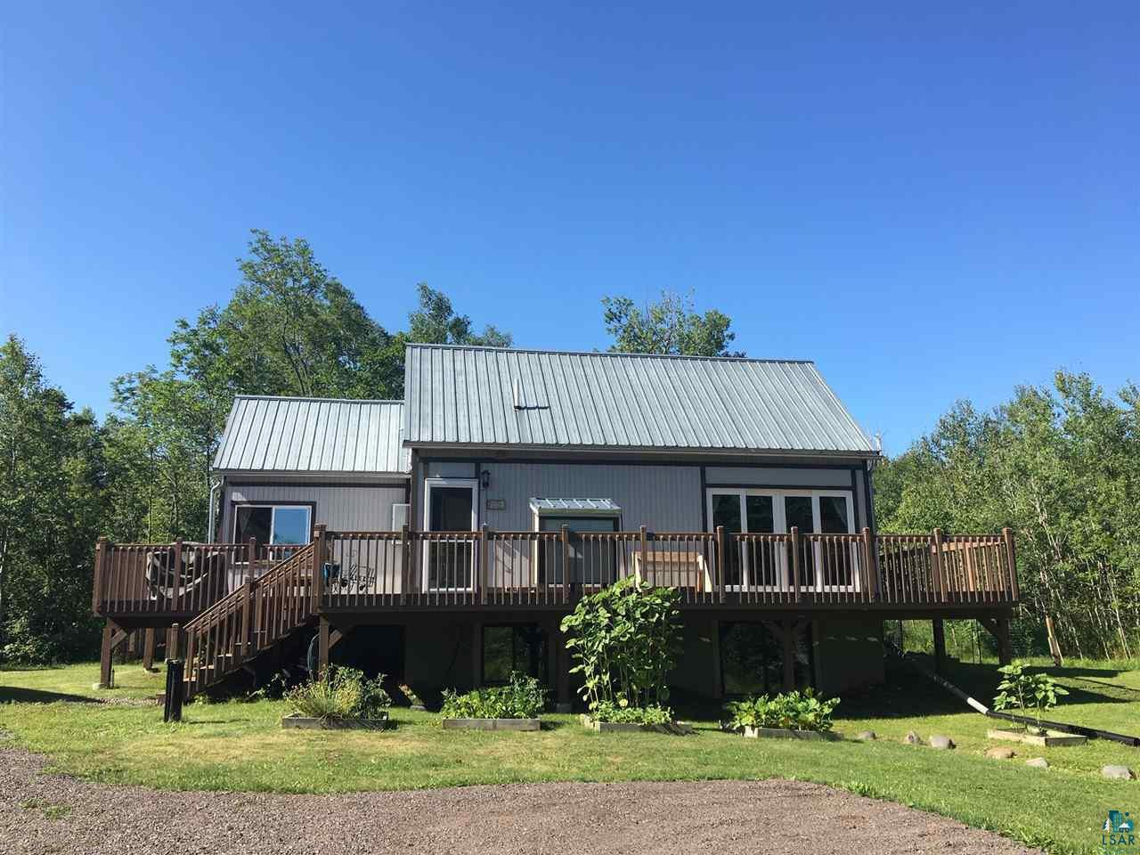 A very original house on 10 beautifully wooded acres, just a stone's throw from Lake Superior! This fun home has so much to offer with open and light living areas, two gas fireplaces and a full (800+ft) wrap around deck. It caters to excellent year 'round or vacation living. Fiber-optic internet makes this a wonderful get-away and work-away option. The living room has vaulted ceilings, two deck doors, lots of light and good flow. There is a large loft to play, work, or add sleeping area. The lower level was newly finished with two bedrooms and a full bath. Utility room and laundry are in the lower level. The back yard is fenced in for safe kid and animal play. There are trails cut through the property, to walk and enjoy the beautiful northern seasons. 3.5 miles from Port Wing town, beach, and marina. 38 miles from both Superior and Bayfield. You are smack-dab in the middle of goodness here, come and see!