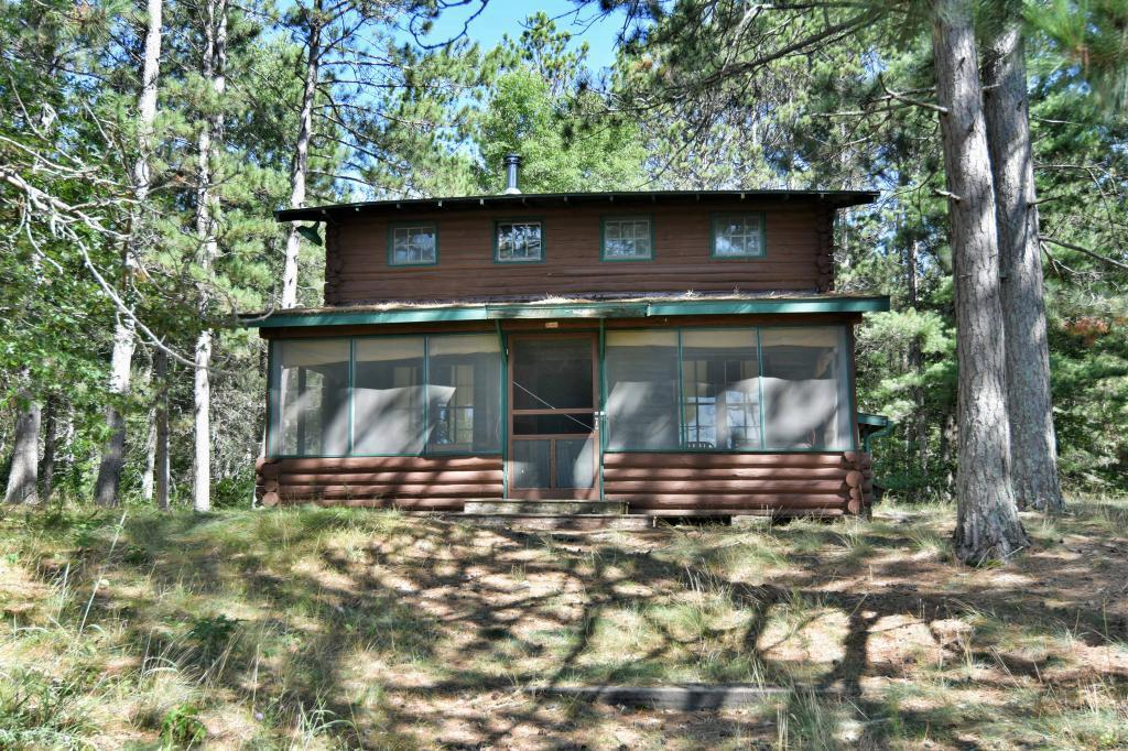 This is truly one of a kind. Not often does one see the beauty of over 29 acres of woods with approximately 2667' of sandy beach with level elevation. Step back in time with a unique log home. Great room with soaring ceilings, massive fireplace and open log staircase. 3 bedrooms & full bath. Kitchen. Take a seat on the screen porch with views down the length of Gilmore Lake known for clean water. It is a part of history and your future in your own retreat in the great northwoods