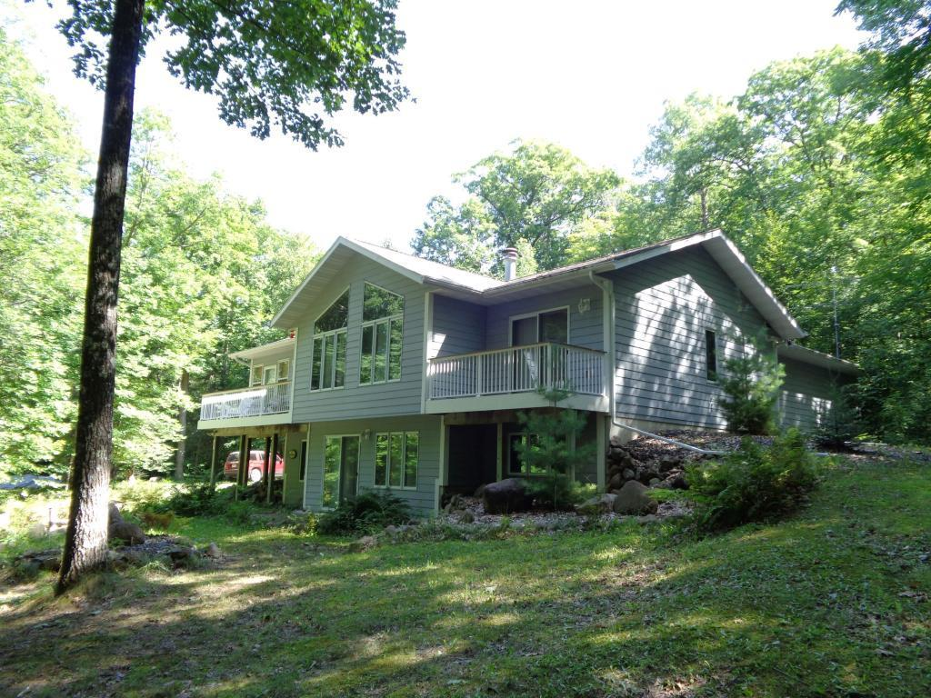 This unique listing comes with a beautifully maintained home and a charming neighboring log guest cabin, nestled next to 2 more additional wooded lots for a quiet and private retreat. The main house has open concept living with 4 bedrooms and 2 full bathrooms, finished walk-out basement, enclosed 3 season porch, 2 TimberTech decks, and LP cement smart siding. The log guest cabin has 2 bedrooms, 1 bathroom and is perfect for your extra guests or a rental opportunity. Just across the road, sits a prime buildable lakefront lot with 0 elevation and a gorgeous sandy beach, perfect for viewing the stunning sunsets on desirable Whitefish Lake. A total of 5 beautiful lots make this an incredible value!