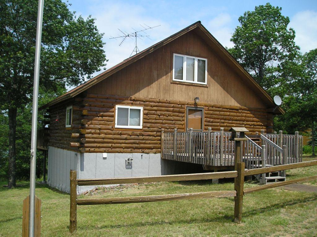 A true up north log cabin in a quiet setting on 200' frontage & over 2 acres. At the end of a cul-de-sac, no neighbors close. Sand based shore. Thousands of acres of county land near by; close to snowmobile and ATV trails. Chalet style, rustic interior. Lakeview deck at main level of cabin plus deck 7 steps to 2nd level & a third deck & steps to the lake. Detached 24 X 30 garage. Fire pit and sitting area in the yard. Level sand beach areal lakeside. Includes most all furnishings