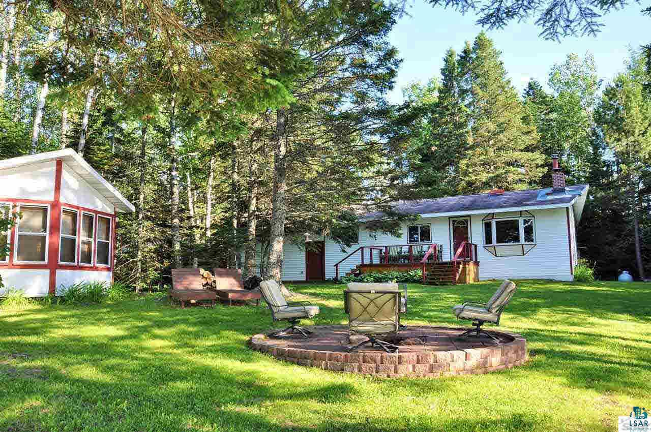 """Cute, cozy and immaculate perched upon 255 feet of Lake Superior frontage...add up to a golden """"opportunity""""! Nicely appointed home/cabin with big windows that bring in lots of light but also bringing BIG Lake Superior views into your living room. One bedroom with a den with pull out coach and guest cottage there is still room for guests. Gather around the large lake side fire pit for good conversation and/or gazing out over the North Shore horizon.  Panoramic vista views that stretch as far as the eyes can see!!! Main floor laundry and attached 2 car garage for additional value. Don't miss this Golden Opportunity...call to schedule a showing today"""