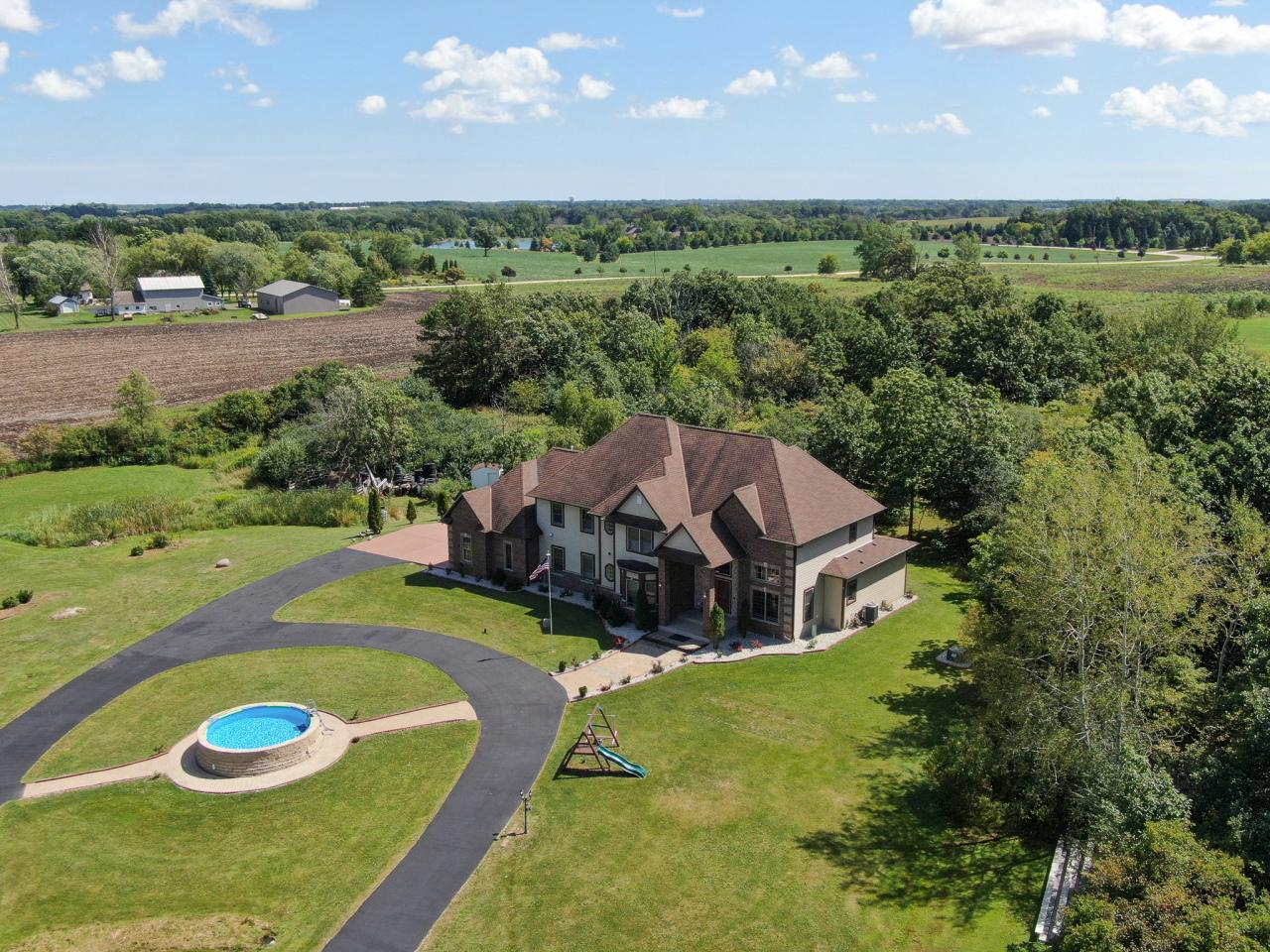 When driving thru the Two Stone Gates you will see this Unique Stately Home with Endless Possibilities. Private 6+ acres, this 4,200+ home has it all. All new flooring on first floor, open concept, new 2 story stone fireplace, gourmet kitchen with wine bar. Master bedroom on first floor with sitting area and completely redone bath. Custom brick and tile work thru out the home. Loft area and extra bonus room/exercise/playroom. Plenty of light, patio doors lead to massive stone patio with outdoor kitchen. Great entertaining space that is very private. Even the garage space has been redone. Too many updates to mention. This is one of a kind. Quality craftsmanship and pride of ownership shows in this custom home. Home Warranty Included for peace of mind.