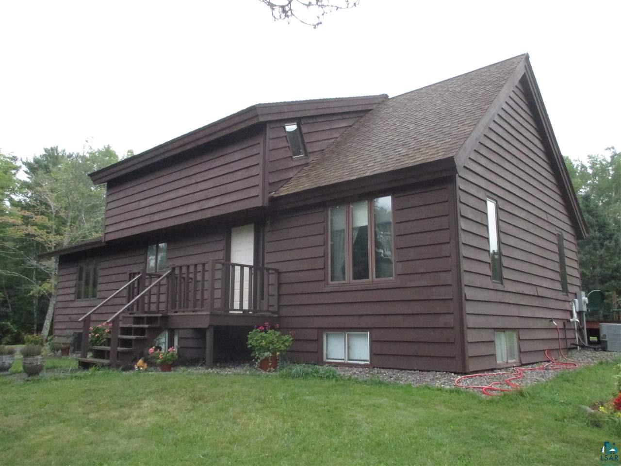 """Cornucopia headquarters! Wisconsin's northernmost town, gateway to the Apostle Islands & the Sea/Ice Caves. This well-maintained home is an easy walk to fantastic beaches, marina, Siskiwit River, shops, dining & near state & county natural areas, trails & forests. Solidly built 2-story home has a living room with an open staircase and cathedral ceiling, beautiful solid wood walls in some rooms and gorgeous Alder kitchen cabinets. Upper loft area has two sweet areas for study or reading, plus two bedrooms & full bath. Main floor bedroom plus office/den with laundry, or use as bedroom. Lower level has two bedrooms plus recreation room & a huge storage/utility room. Very energy-efficient, with southern exposure & 3 cedar decks. Detached two-car garage plus HUGE 30' x 48' """"stick-built"""" storage building with 8"""" thick concrete floor, 12' sidewalls, 3 10x10 overhead doors so you can drive right through! Circular driveway with new gravel. This site is nicely sheltered from the road with pines, spruce, apple trees and a sunny yard perfect for flowers & gardens. Make this your headquarters for fishing, kayaking, sailing, birding & all kinds of winter activities. Perfect setting for a home-based business with high-speed Internet, excellent exposure & outbuildings. Or just kick back and enjoy this friendly little community and get to know your neighbors!"""