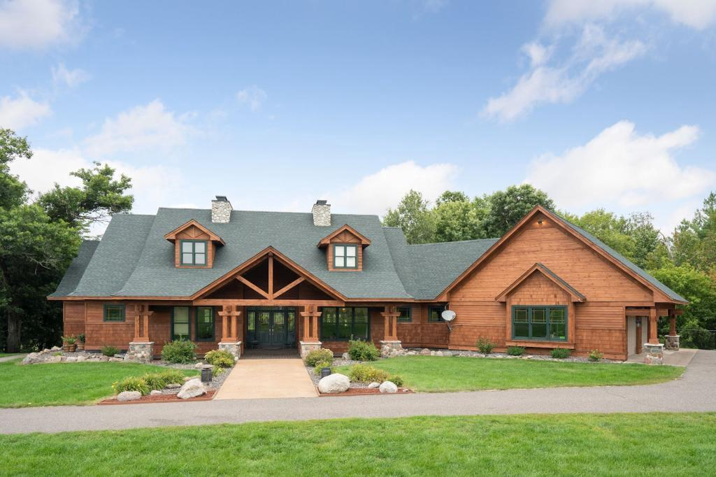 Executive level home/lodge/retreat built mindfully with a keen eye for attention to detail with 5600 finished sq ft. Every custom feature in this beautiful home is unique and perfect. Over 14 acres of scenic privacy and abundant wildlife on the banks of the meandering Wood River and a unique Artesian well in your backyard. Geo Thermo heat pump with in-floor heating throughout the home. This property offers a guest house,(2) 54x36 detached sheds, totaling 11 garage stalls. Slightly over 1 hour to the Twin Cities. Perfect landscape for the horse enthusiast, livestock can graze and water themselves.