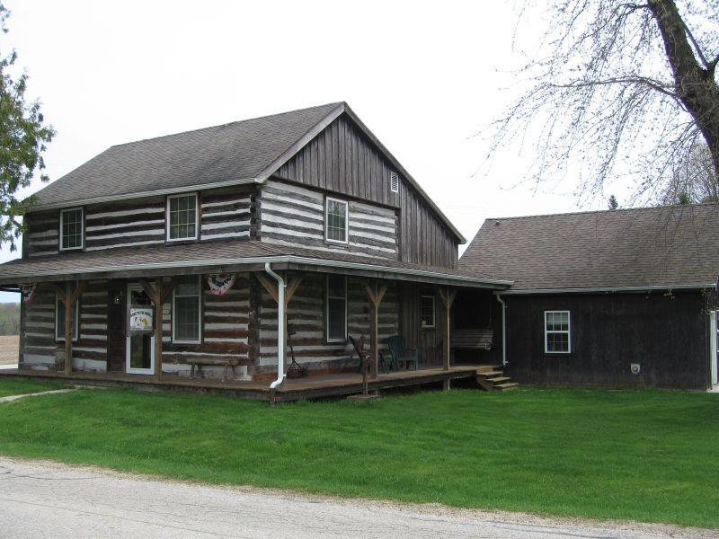 Now is the time to own your piece of history w/ this one of a kind, 1860 log home . Tucked in the Kettle Moraine hills, you can enjoy the best of both worlds.  Country living  w/ close proximity to state parks, trails, & lakes or city life just moments away to enjoy the arts, entertainment & shopping. This fantastic home has been lovingly cared for over the years offering glistening hardwood floors, exposed timbers & a fantastic floorplan.  Handcrafted artisan elements are found in the kitchen cabinet details, metal ceiling in the formal living room, custom doors & a loft overlooking the open concept family room w/FP.  This property also offers a 3 car attached garage & an attached shop currently used as a dog grooming shop.  The adjacent pole barn provides endless opportunities!! Must see
