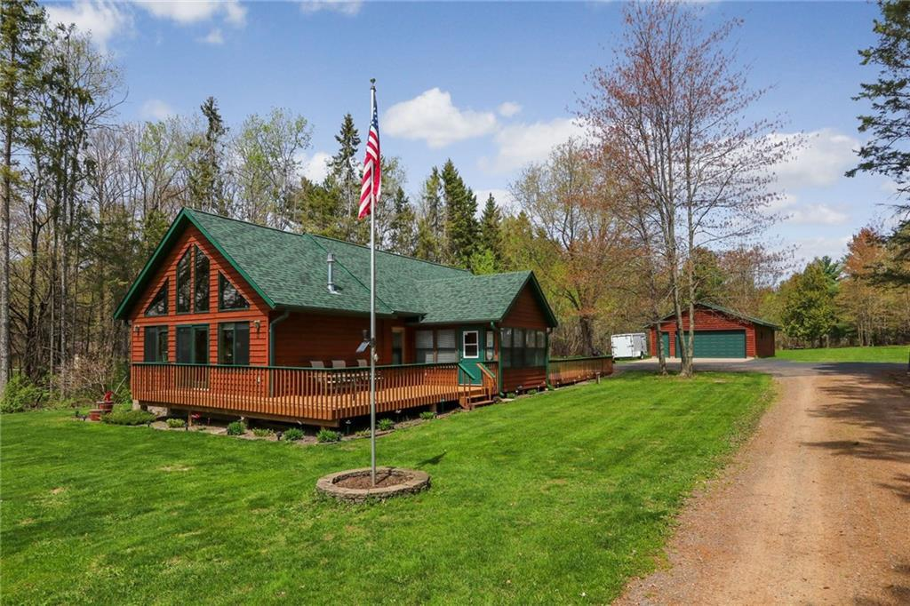 Efficient updated 3bdrm/2ba Chalet with vaulted knotty pine ceilings, fireplace, air conditioning, and 3 season porch all on 3+ acres! Located on desired Sand Lake with South facing & level sugar- sand frontage. Cabin addition in 2010 and many amenities & updates were added. Also a new roof in 2016 & stained in 2018.  There is a 2+ car oversize garage heated with workshop and another 20x20 garage, for lots of storage! Right near Snowmobile trails,  several golf courses, & many great restaurants. Only about 20 minute drive to Hayward or Spooner, and about 2.5 hours to the Twin Cities area. Impeccably maintained and many efficient features added. (Hwy runs between cabin and lake and the low property taxes reflect that.)
