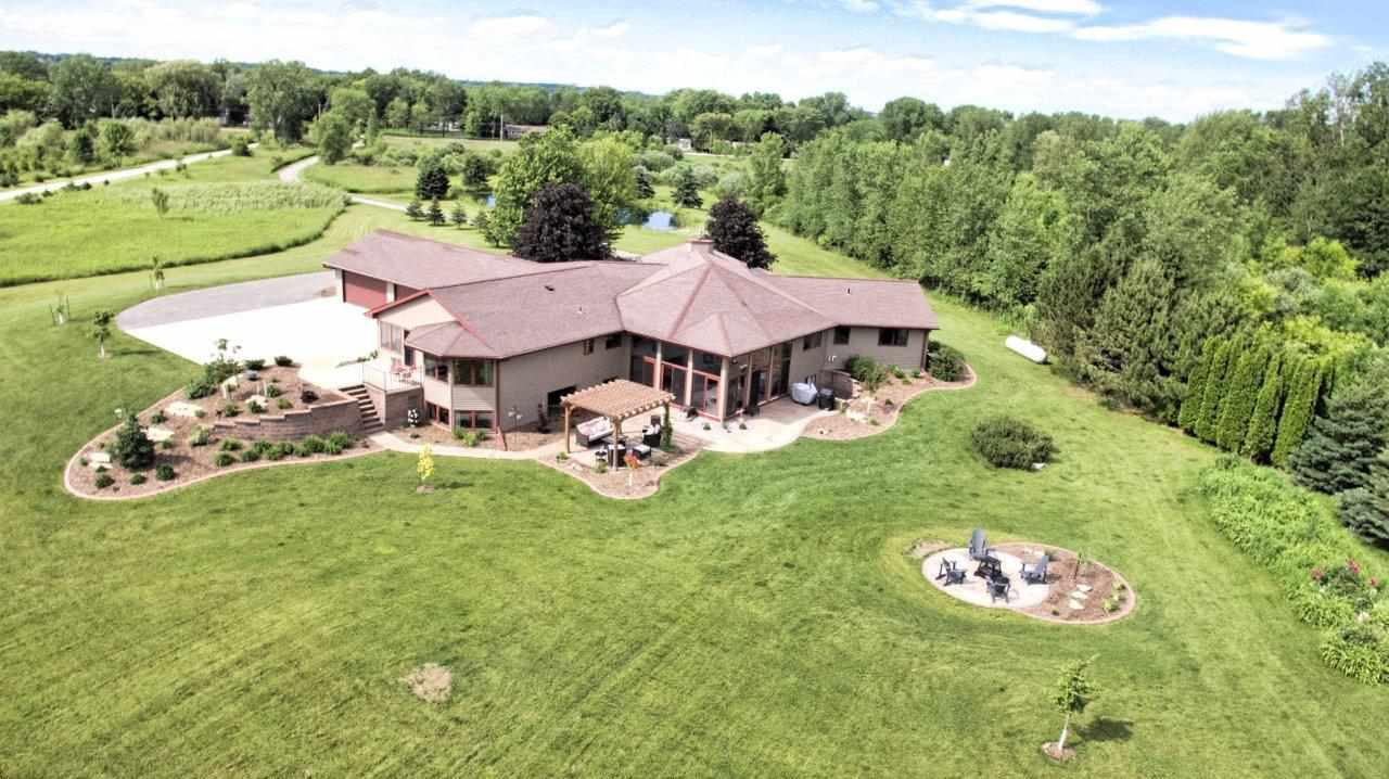 """Set back on almost 10 acres you will find this magnificent 6000 sqft walkout ranch. High ceilings,angled rooms,pillars,water feature & open concept give this beauty a unique flair. Large windows offer scenic views. 5 spacious BRs w/walk in closets, 4.5 baths & a expansive family room in LL perfect for entertaining. """"Other room"""" is mother in law suite w/0 step entry. Enjoy hot tub in solarium or relax in outdoor living space that boasts stamped patio, pergola, professional landscaping & separate seating/fire area. 2 ponds, 4 car garage w/turn around driveway. $12,500 kitchen allowance."""