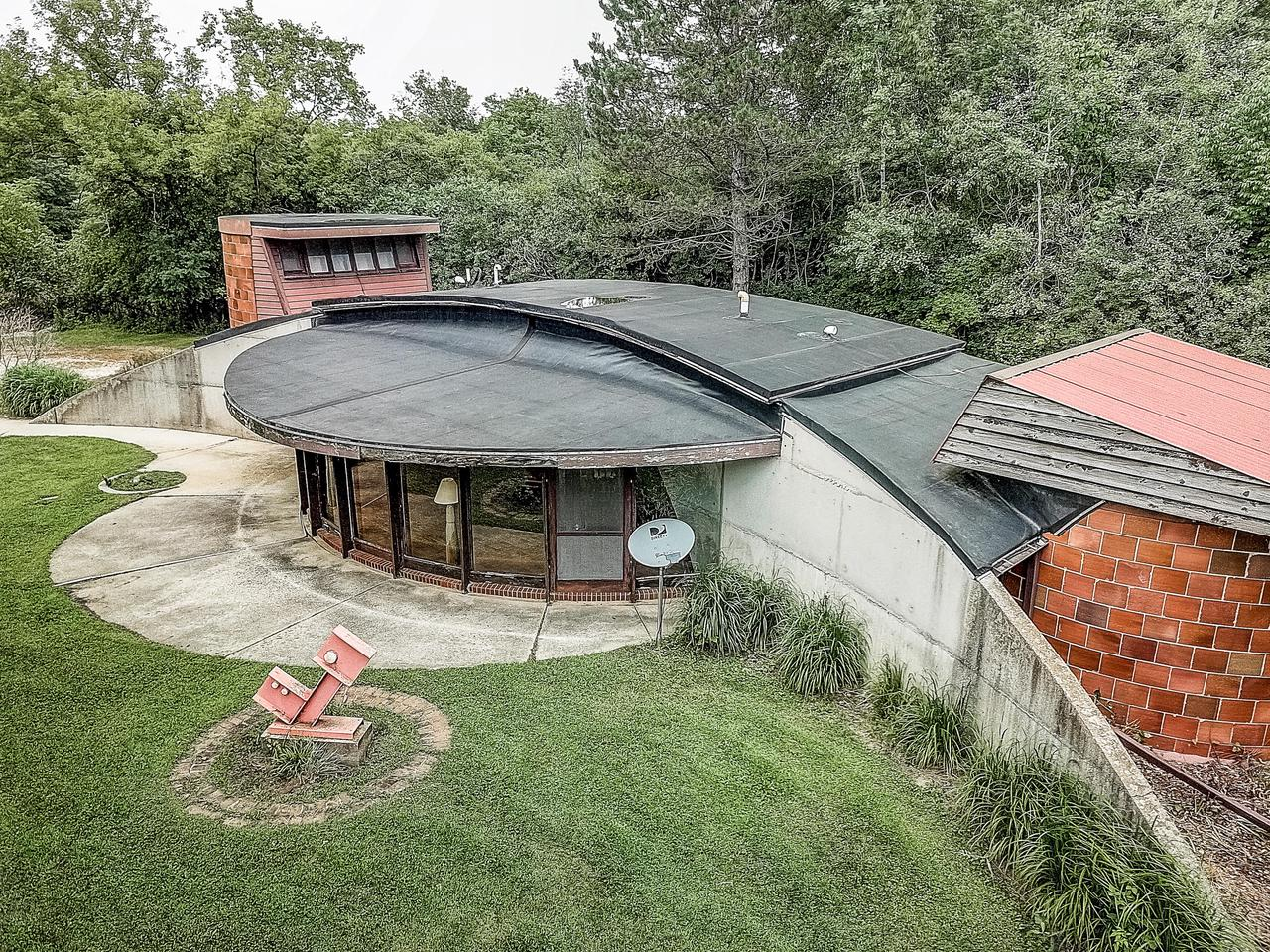 This one of a kind expressionist modern style home was custom built in 1969. The curved lines throughout the home harmonize a space that is fully open concept, yet still provides individual space. Enjoy the scenic/private views of the outdoors from the curved wall of windows in the living/dining room. Each end of the home has a circular shaped bedroom that the exterior walls are constructed with large bricks originated from a concrete silo in norther Wisconsin. Ladder in master bedroom connects to home office. Improvements in this home include Water Well pump (18), furnace & H2O heater (16), C/A (12). The property rests on over 4 acres (vacant lot next door with 2.11 acres, could be purchased together for additional $98,000: Lt. 2 Sconfinato Dr). Home being sold as-is condition.