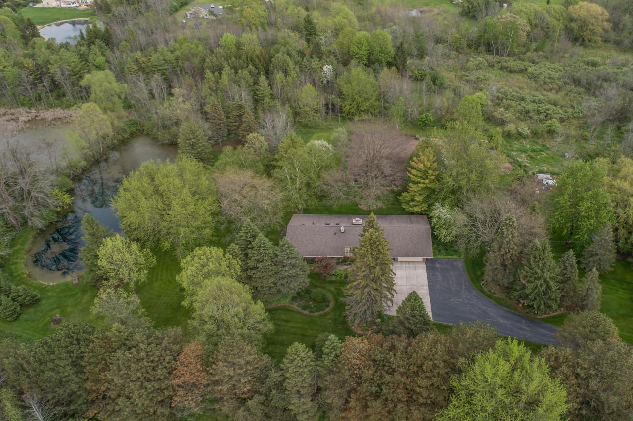 Attention City Dwellers or Country Folk! This private, 8 acre retreatfeatures 'a treasure of a home' snuggled in a choice location, yet is only 3 minutes to I-43 and less than 25 minutes to downtown Milwaukee! Thisbeautiful contemporary ranch exhibits high quality construction/attention to detail throughout.The 'park-like' parcel is excitingly special, unique and very attractive! Quartz & Corian counter-tops, birch cabinetry, hardwood flooring, updated baths, heated tile flooring, walk-in shower, NFP, huge closets, main floor laundry & much more! Newer heating and cooling mechanical systems provide peace of mind and comfort. There is a huge enclosed breezeway. Outside you will find fenced areas, pole barn, plentiful trees/plantings and interesting land to make this property your own.