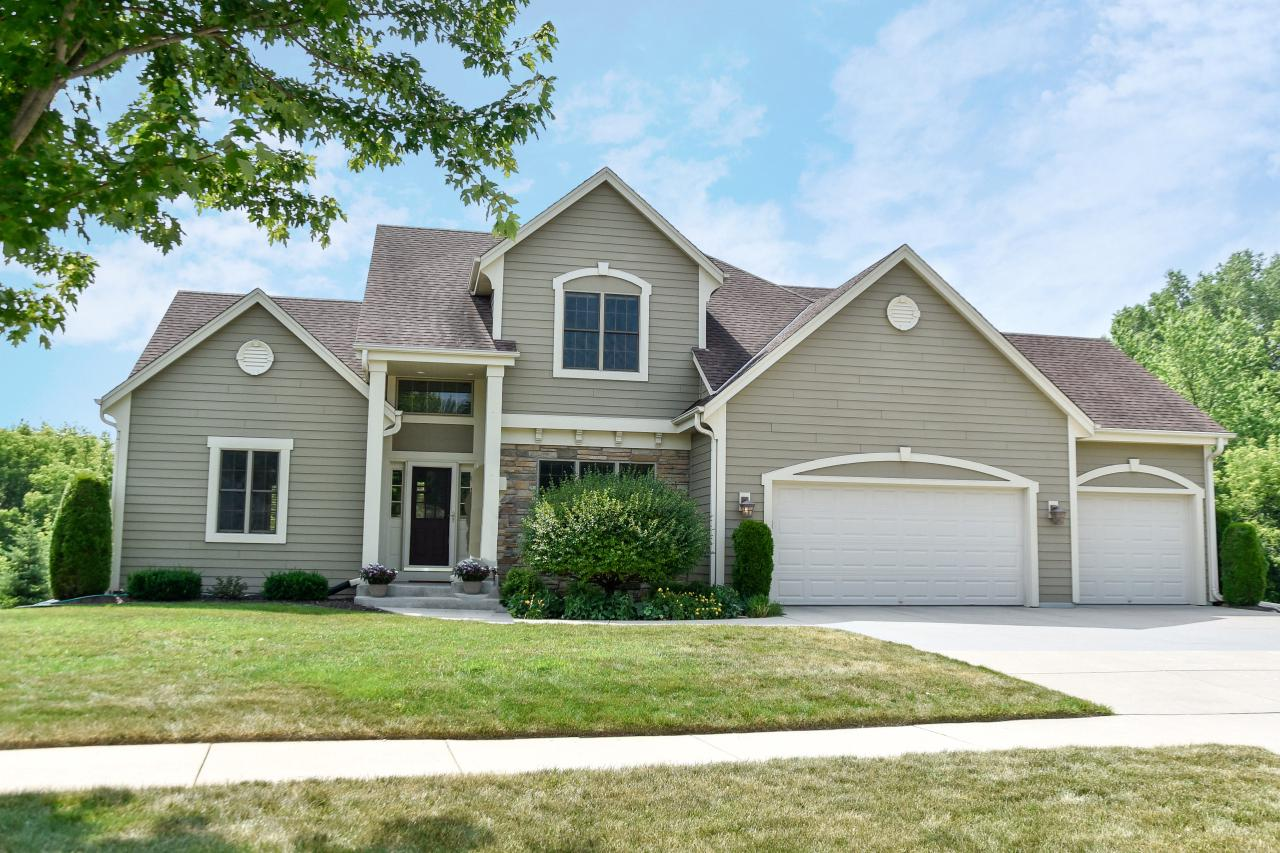 This beautiful custom built home Trustway home in Blackhawk Valley offers some of the best views in the neighborhood. Experience classic detail in the abundance of hardwood floors, crown moldings, & arched entries. Relax in the generously sized great room featuring a beautiful gas fireplace & vaulted ceiling. Open concept great room to kitchen. Chef's kitchen featuring white custom cabinetry, prep island, walk-in pantry, SS appliances, & sunny dinette.  Retreat to the elegant first floor master suite with trayed ceiling & private spa bath. 1st floor laundry. Three very spacious bedrooms with walk-in closets up. Entertain friends in the spectacular walk-out lower level featuring a second family room with another fireplace , a wet bar with beverage & wine fridge, an office & extra full bath.