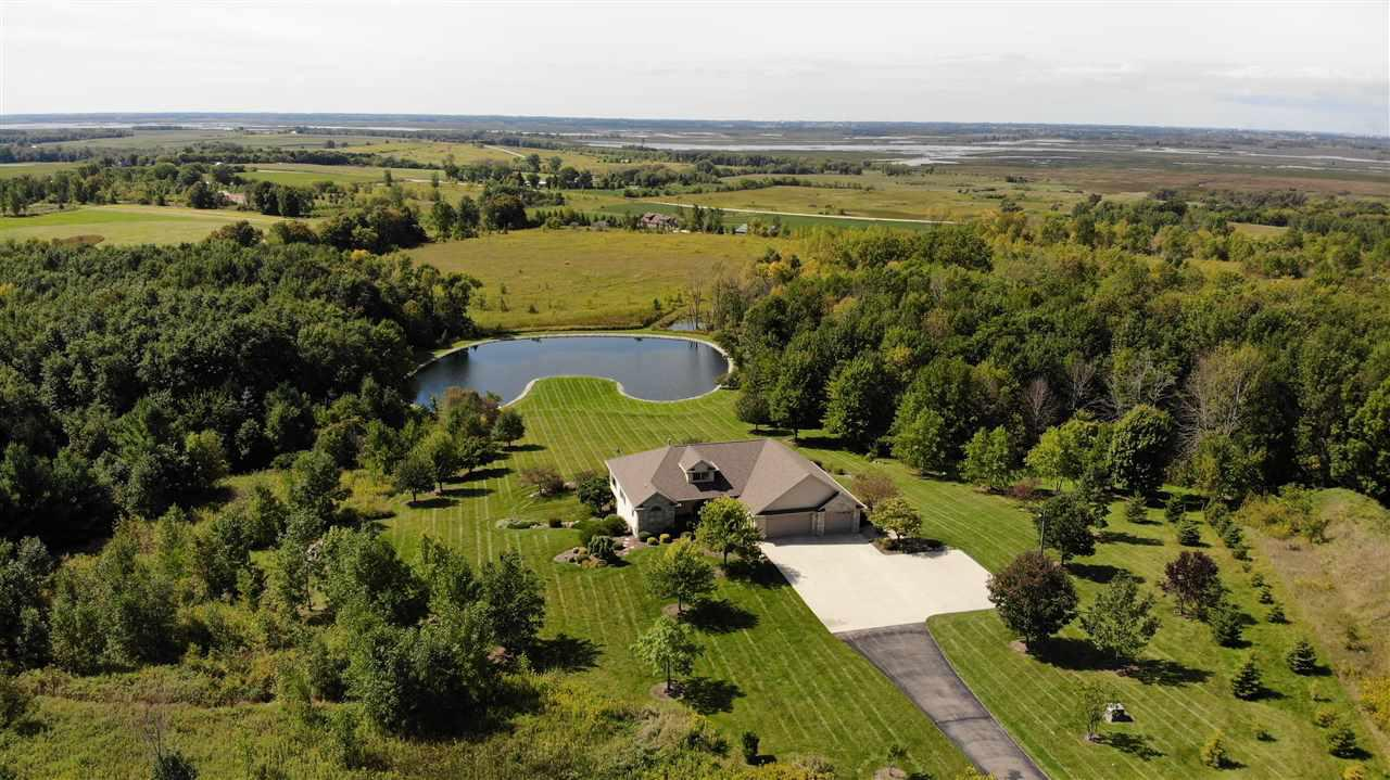 The magnificent views from this custom built 2-3 BR walkout ranch home on over 35 gorgeous acres w/ a riprap pond are as good as you'll find in this state! It overlooks the Horicon Marsh and has abundant wildlife that will certainly impress the outdoor enthusiast. One look at this property from the 18X16 composite deck & you'll be hooked! Its truly one of a kind w/ a 2 story garage & a Control4 whole home integration system that's technology lovers dream. Its very efficient w/ its geothermal system & zoned in floor heat. Amenities featured are too expansive to list! Its a must see!