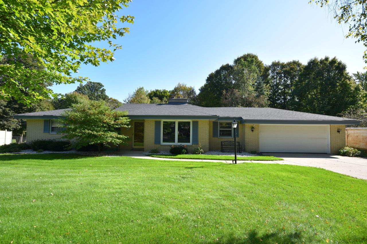 All brick mid-century gem on oversized lot! This home was meant to entertain year round. Natural light floods your huge living/dining room area featuring a double sided fireplace and built-ins (HWF under carpet per seller!).  On the other side of the fireplace is a cozy family room with views to your new pool and the eat-in kitchen.  All 3 bedrooms have hardwood floors, and the master features a walk through 1/2 bath for convenience, plus check out the updated full bath! Owners have added an egress window to the lower level, which currently features a rec room with bar, and is ready for expansion. Furnace, stove, pool, bathroom, some flooring, egress, lower patio and walkway all done in the last 2 years.