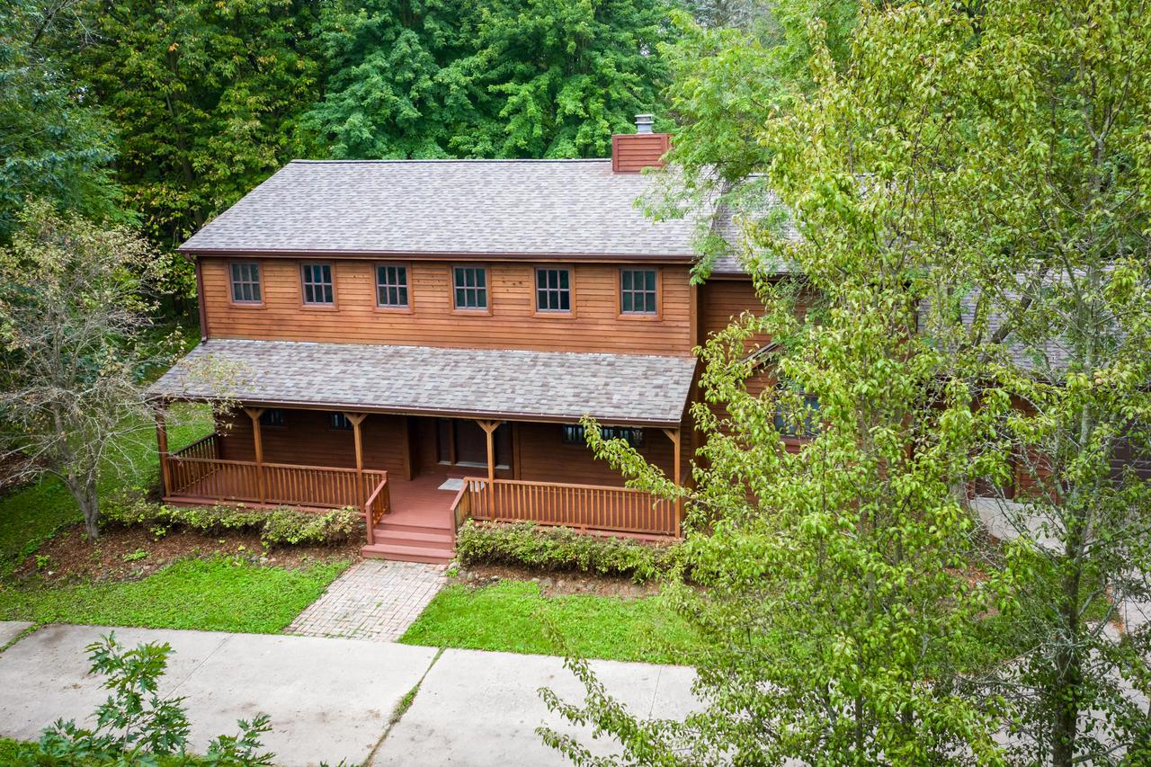 Over 10 acres of wooded paradise.  Enjoy all the space in this over  4000 square foot log home.  5-6 bedroom home with 2 bedrooms on the main floor and 3-4 Bedrooms upstairs. Main floor Large master suite with huge bathroom.  Large kitchen with breakfast counter and plenty of cabinets and counter space. Enjoy entertaining in the large great room just off the formal dining room. Great room features natural fireplace with an antique surround. Green house off the great room, ideal for winter planting. Finished Lower level features large family room, den/office, 1/2 bathroom and wet bar area with an antique bar and cabinet.  New carpet throughout and exterior has been freshly stained.   Call today for your private showing.  One-year home warranty included.