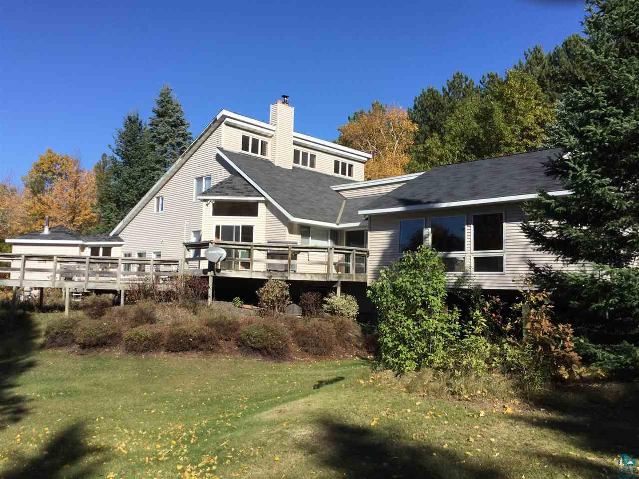 Spectacular west facing views of Lake Superior. Within about an hour driving distance from Superior, WI & Duluth, MN. This spacious home offers privacy located just outside Port Wing near Lake Superior & the Port Wing Marina on 30 forested acres. The main floor features an open living room/dining room/ kitchen, an added spacious family room with fireplace , second dining area & bar,a main bedroom, laundry room, attached two car garage, sauna & hot tub room, lots of closet space, & walk out decks. Gorgeous lake views from the second floor which features two bedrooms, an office space, & a bathroom.  The walkout basement features a bathroom, utility room, several rooms currently used as a bedroom, rec room, & den. The outside features gravel driveway, maintenance free exterior, decks, & fenced in gardens. There is  a large 26x 42 + 20 x 22 Pole Barn with two garage doors & a large sliding door, wood stove for heat, concrete floor, electricity, and a workshop area.  There is a 16 x 36 concrete pad with a shelter logic cover for RV storage.